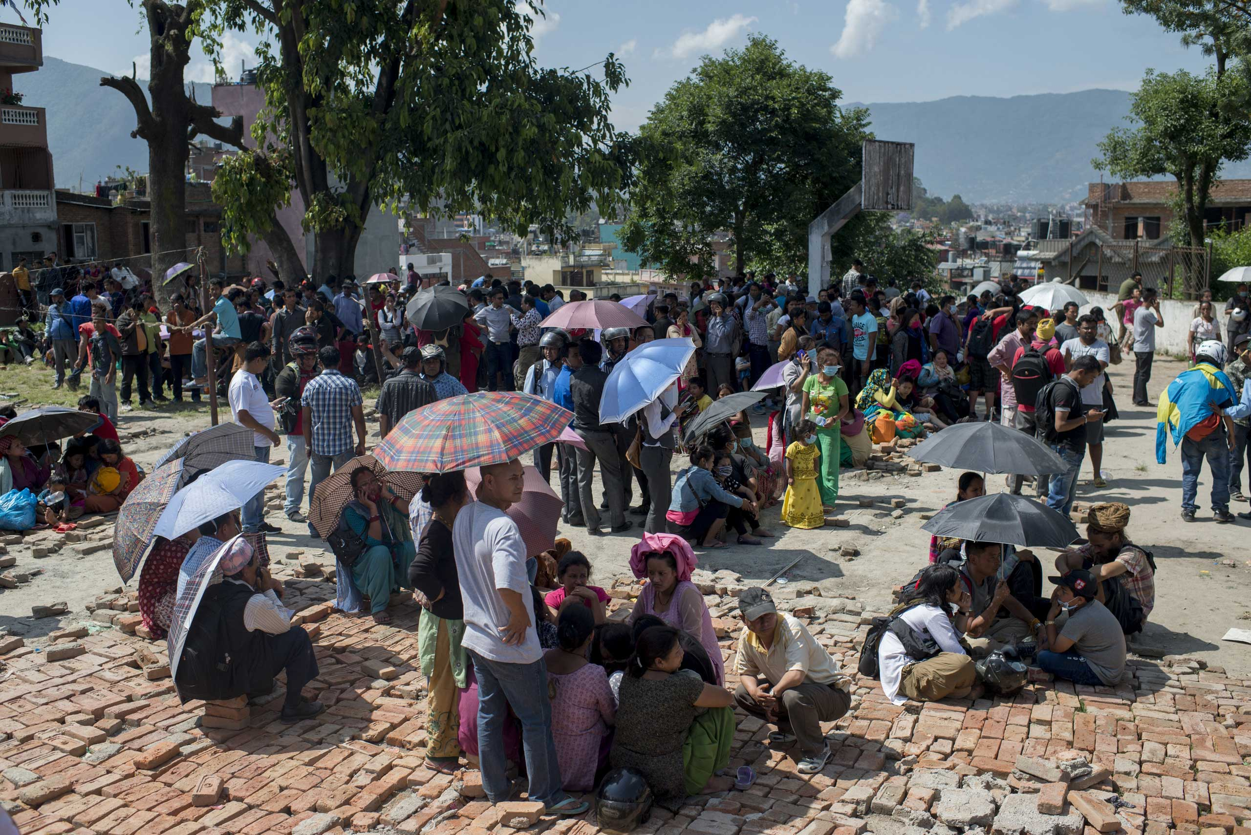 People gather in the safety of open space following a further major earthquake in Kathmandu on May 12, 2015.
