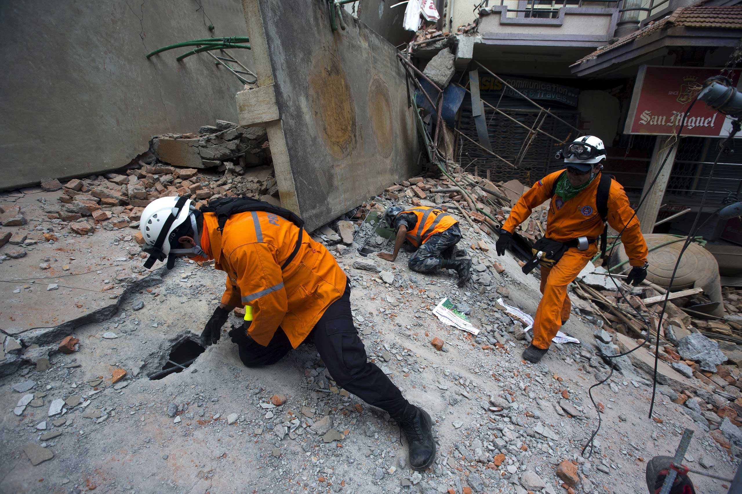 Nepalese military personnel and International rescue check on a collapsed building after an earthquake in the centre of Kathmandu on May 12, 2015.