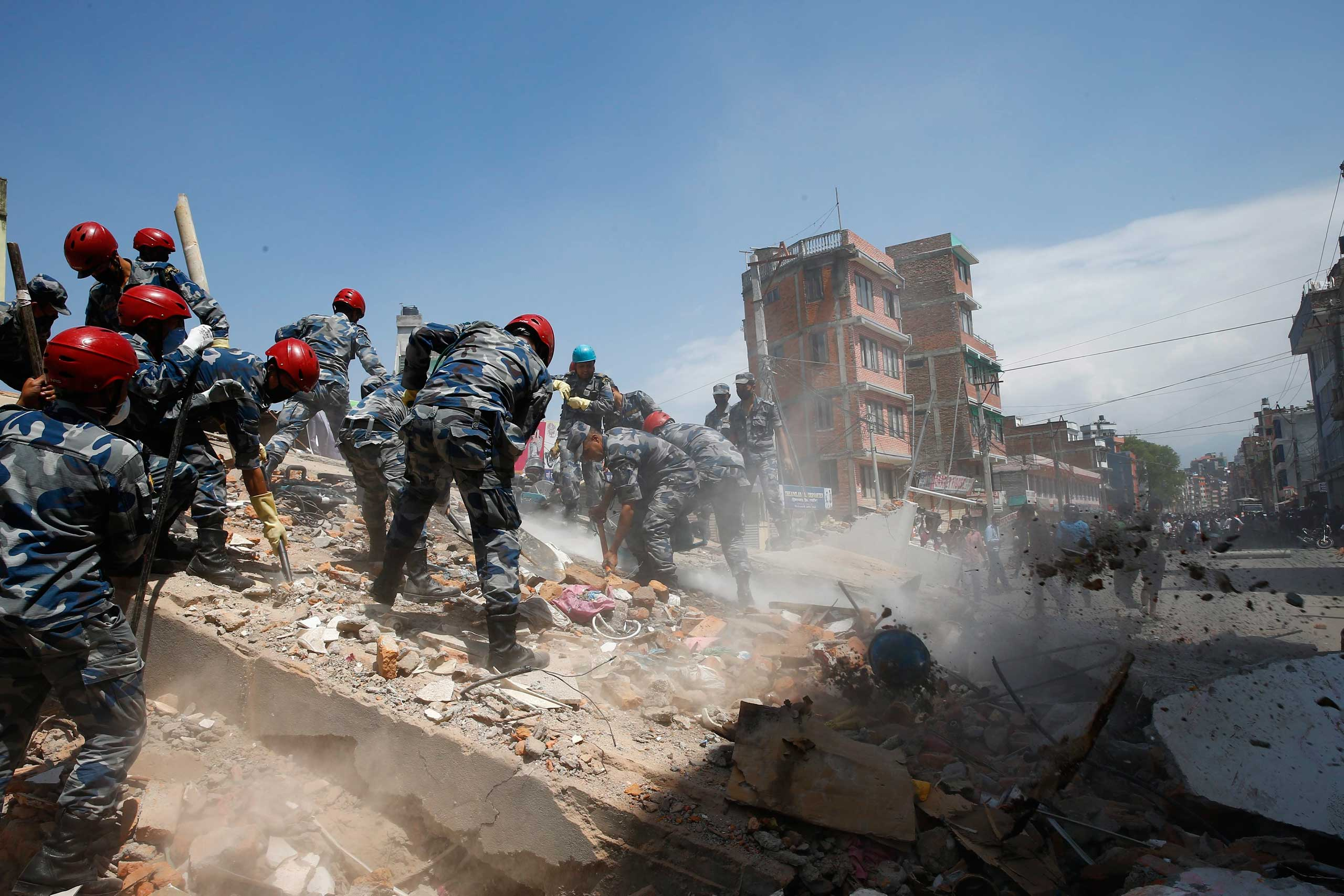 Nepalese armed police force search for victims after a house collapsed in strong earthquake hits Kathmandu on May 12 2015.