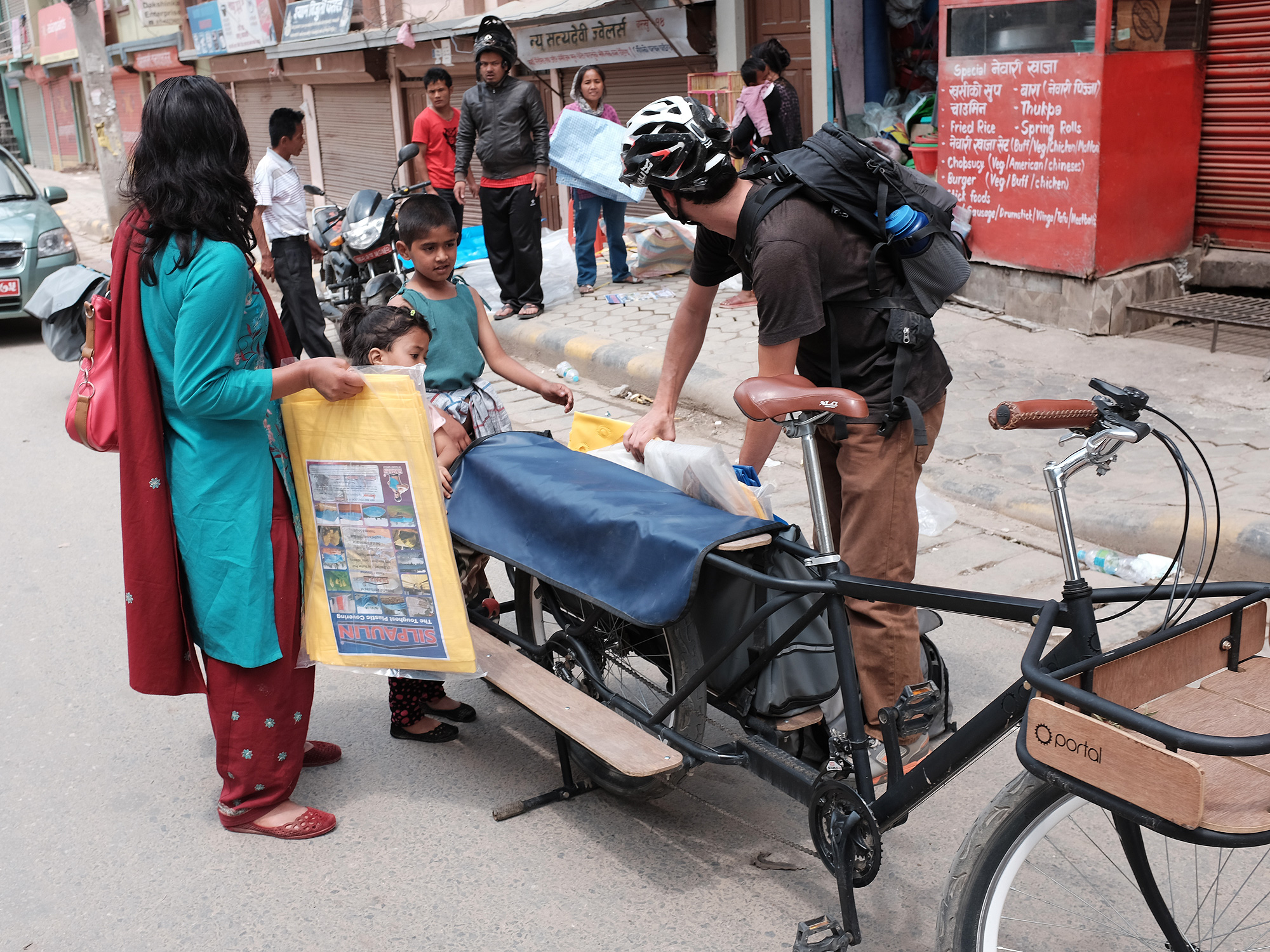 A mountain bike team member hands out tarpaulin in villages in need of relief after the Nepal earthquake of April 25, 2015