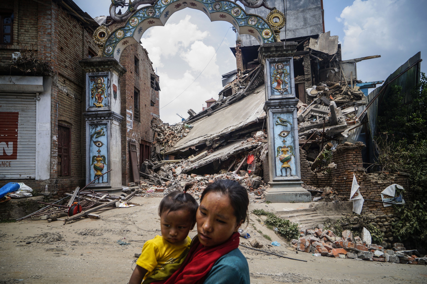 A Nepalese woman carrying her child walks past a destroyed building in Sankhu village in Kathmandu, Nepal on May 16, 2015.