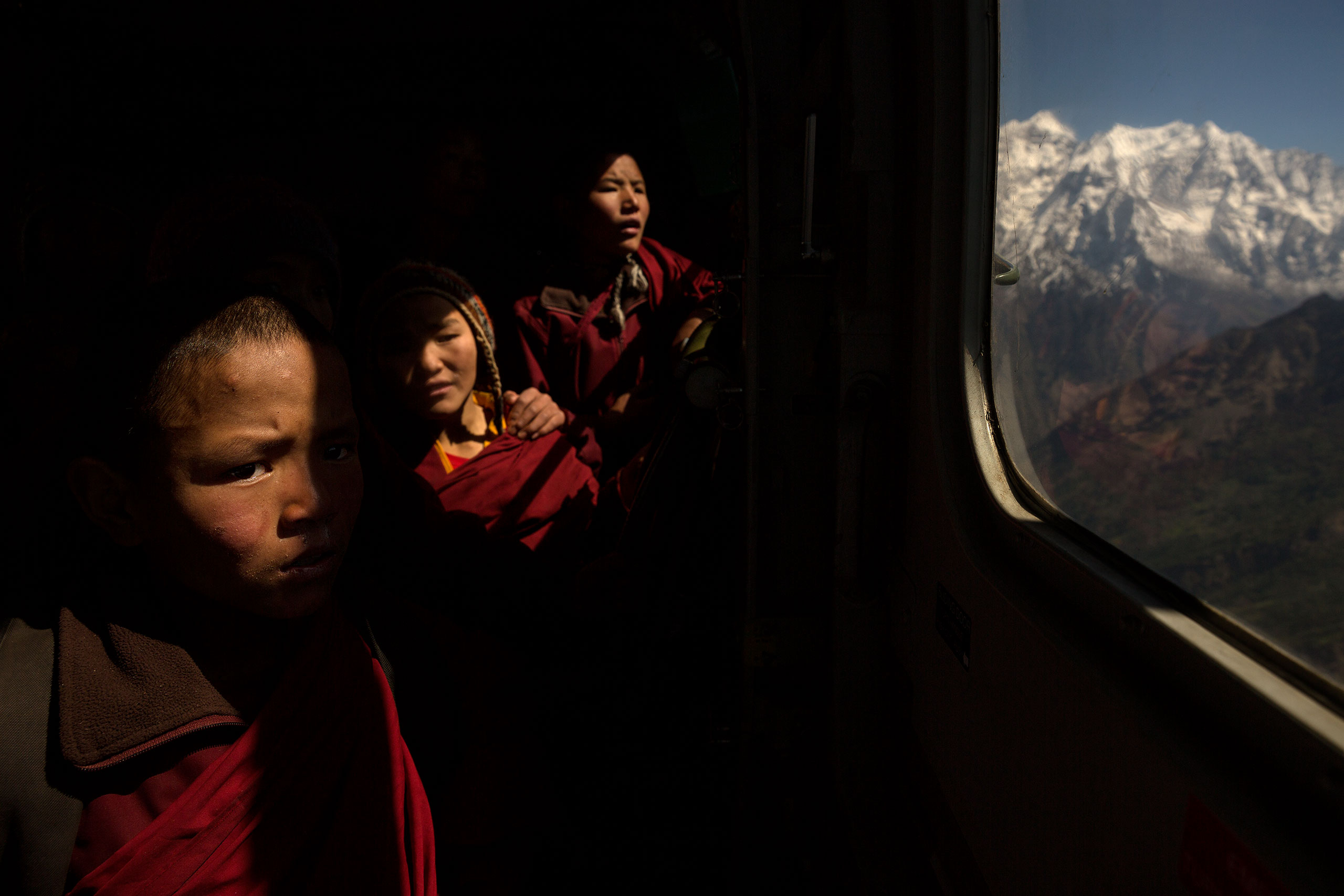 Young Buddhist monks gaze out of a helicopter as they are evacuated by the Indian army from a monastery in the Himalayas, May 2, 2015.