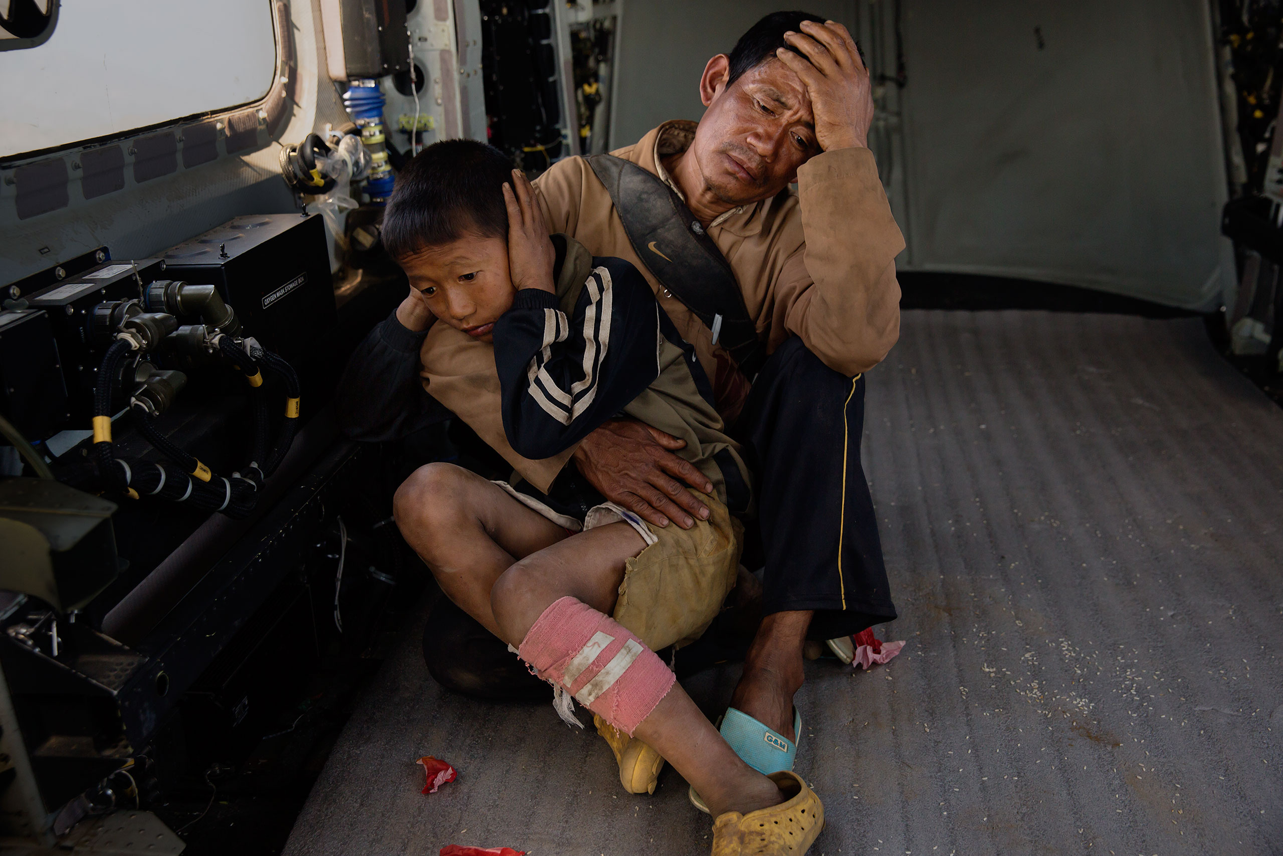A boy who was injured in the mountain village of Dhunchet sits with his father after being evacuated by an Indian army helicopter, May 3, 2015.