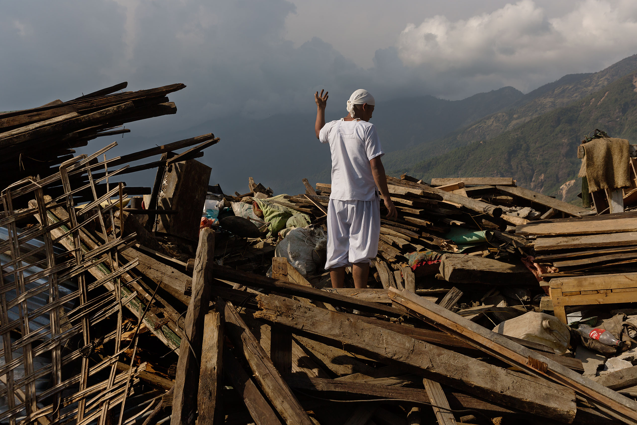 Dhan Raj Ghale, 30, dressed in mourning garb after the death of his mother, looks for possessions from his house in Barpak, Nepal, May 5, 2015.