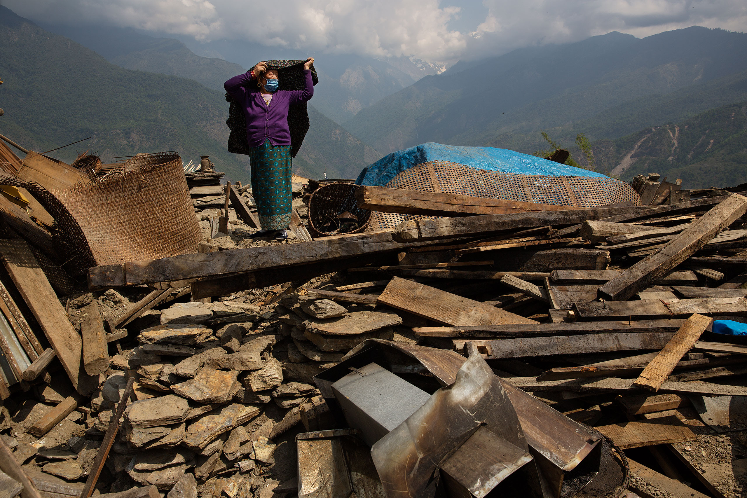 A villager stands among the ruins of the destroyed houses in Barpak, Nepal, May 6, 2015.