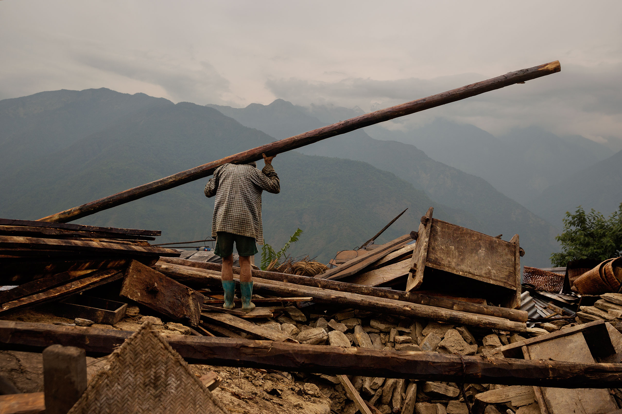 A man lifts debris from a flattened structure in Barpak, Nepal, May 6, 2015.