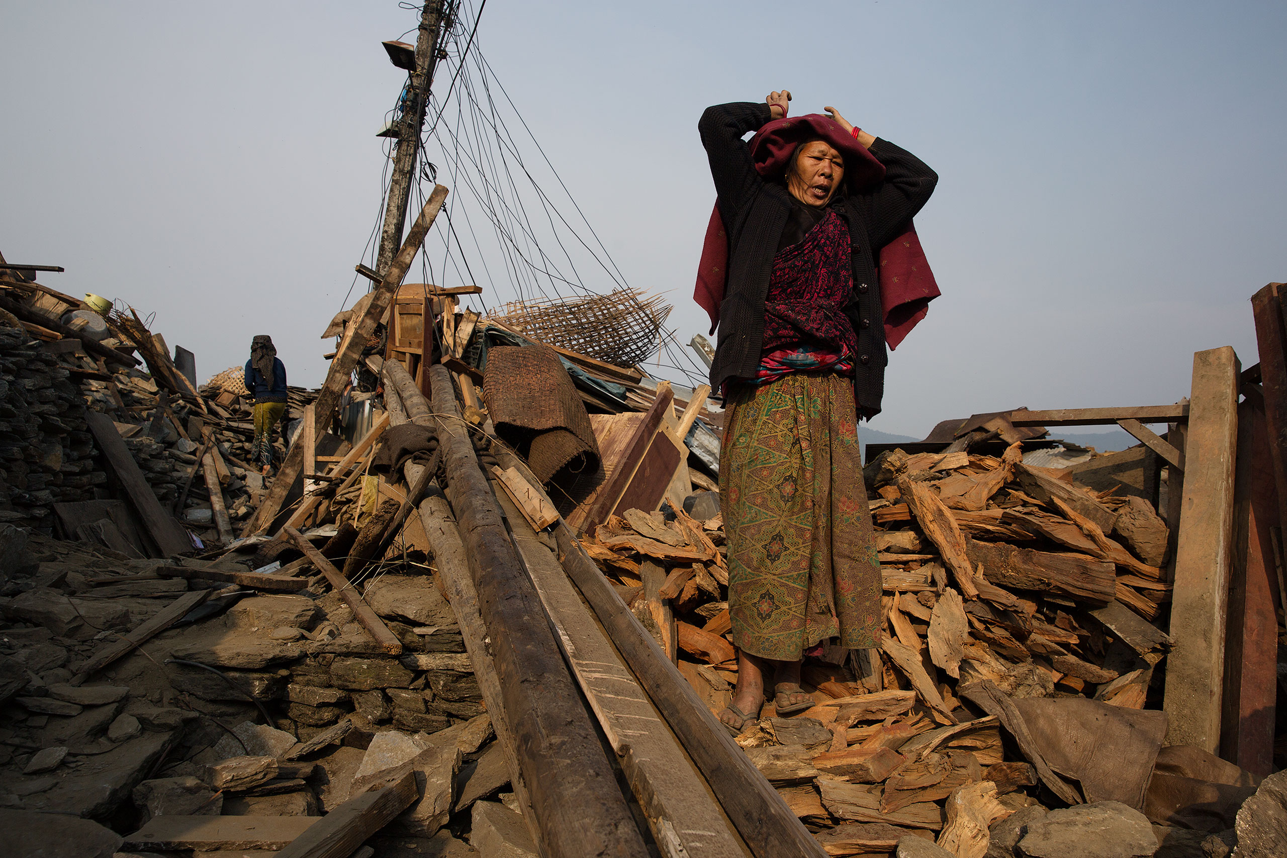 A woman stands among the wreckage in Barpak, Nepal, May 6, 2015.