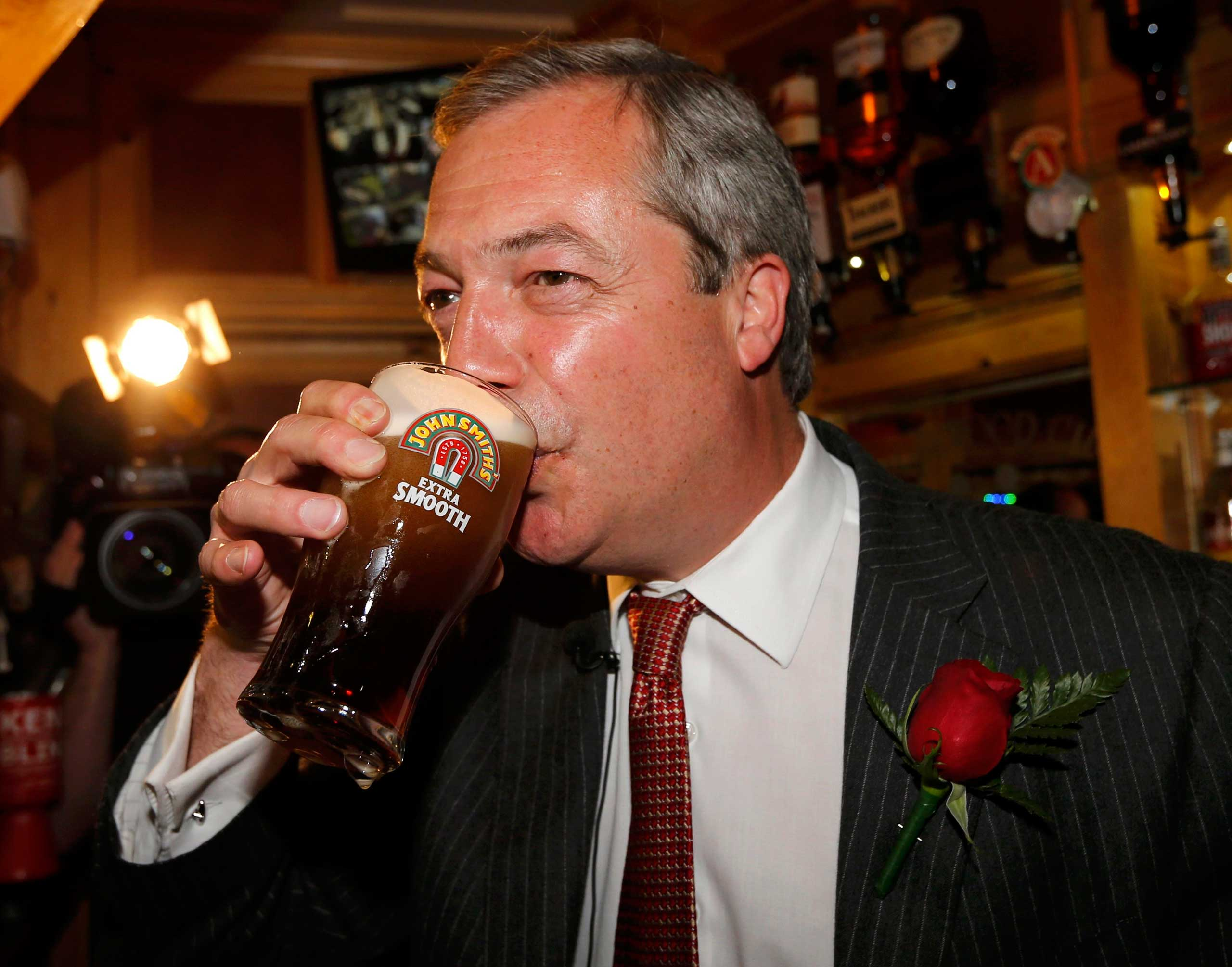 Nigel Farage enjoys a pint of beer during a visit to mark St George's day at the Northwood Club in Ramsgate, southern England on April 23, 2015.