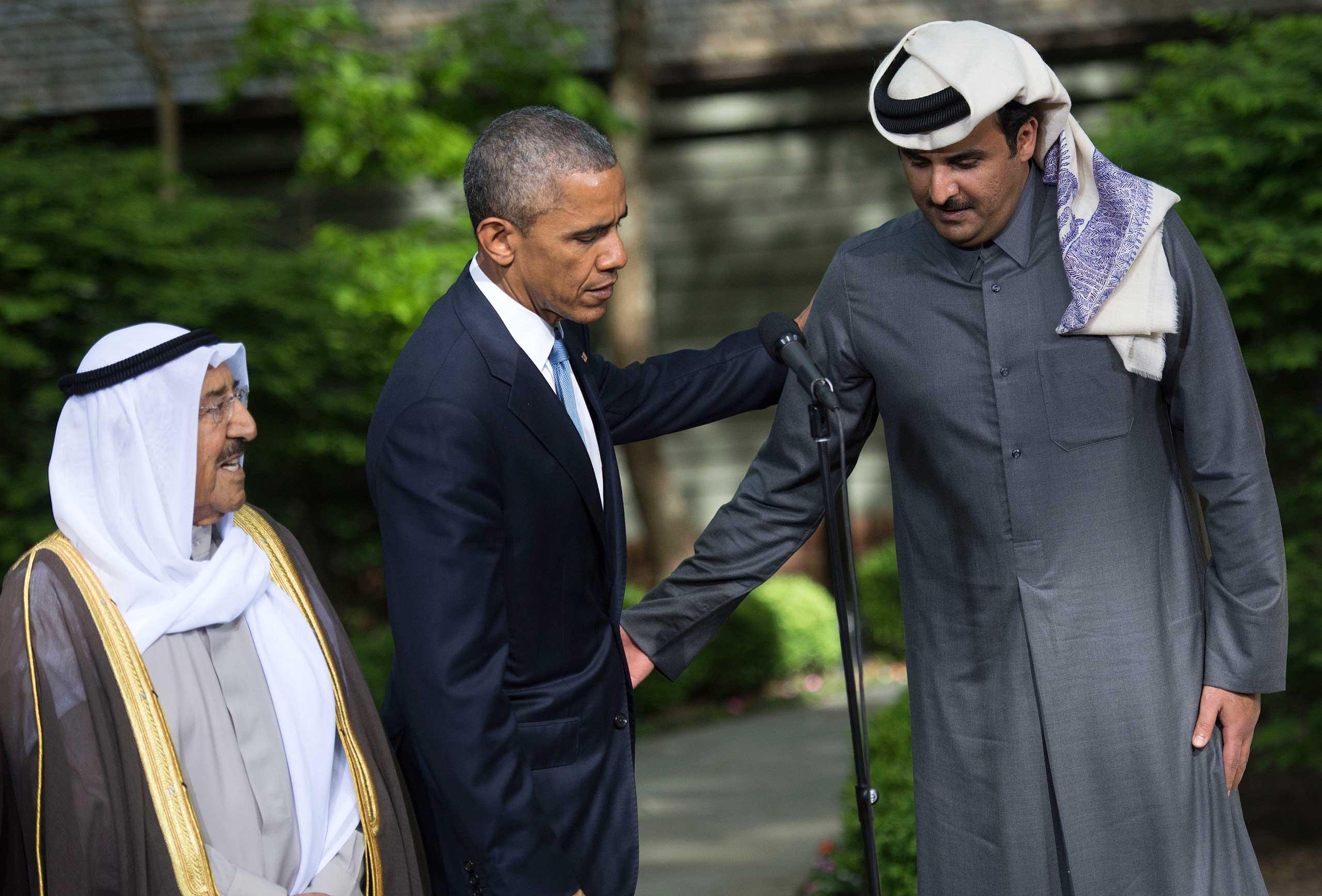 Obama encourages Kuwaiti Emir Sheikh Sabah Al-Ahmad Al-Sabah to make a statement alongside Qatar's Emir Sheikh Tamim bin Hamad Al-Thani, following the Gulf Cooperation Council-U.S. summit at Camp David on May 14, 2015.