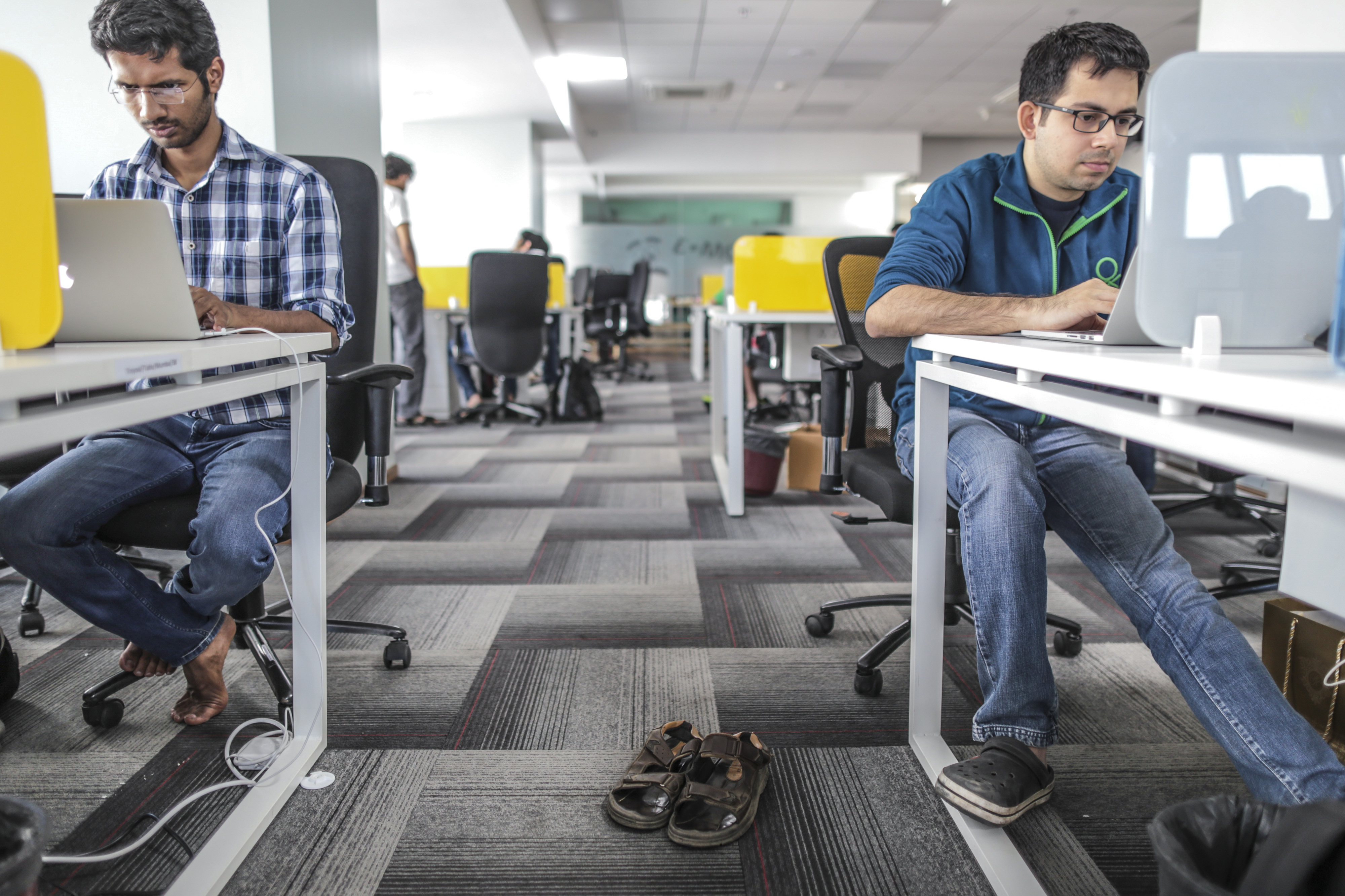 Tiny Owl employees work on laptop computers as pair of sandals sit on the floor inside the company's head office in Mumbai, India, on Monday, March. 9, 2015.