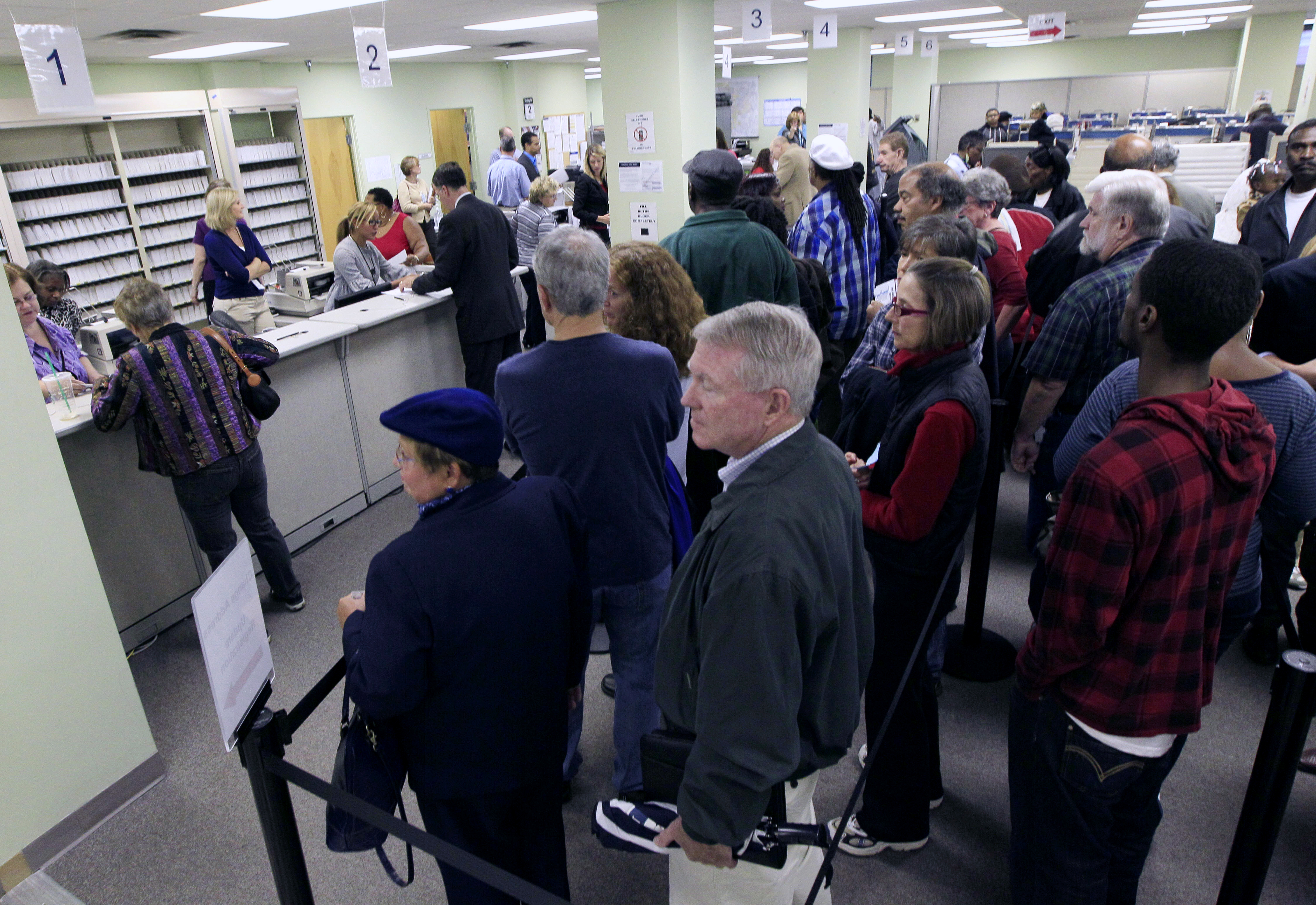 This Oct. 2, 2012 file photo shows voters waiting in line to pick up their ballots inside the Hamilton County Board of Elections after it opened for early voting, in Cincinnati.