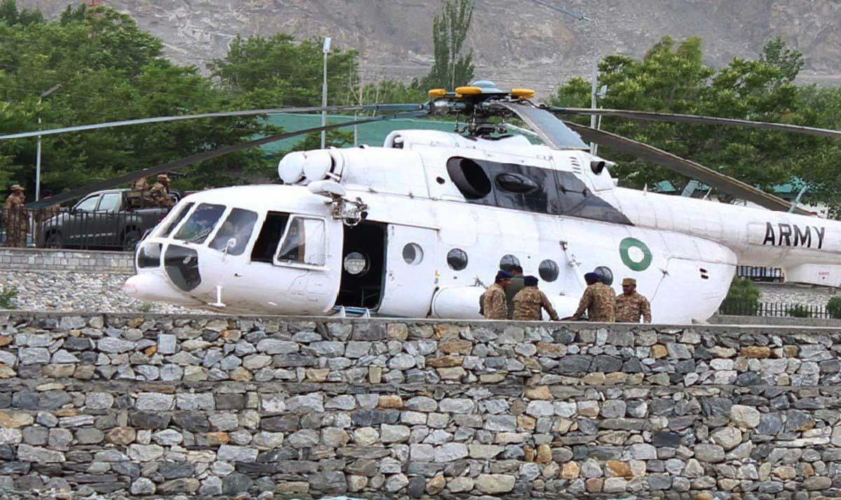 Pakistani soldiers gather beside an army helicopter at a military hospital where victims of a helicopter crash were brought for treatment in Gilgit, Pakistan on May 8, 2015.