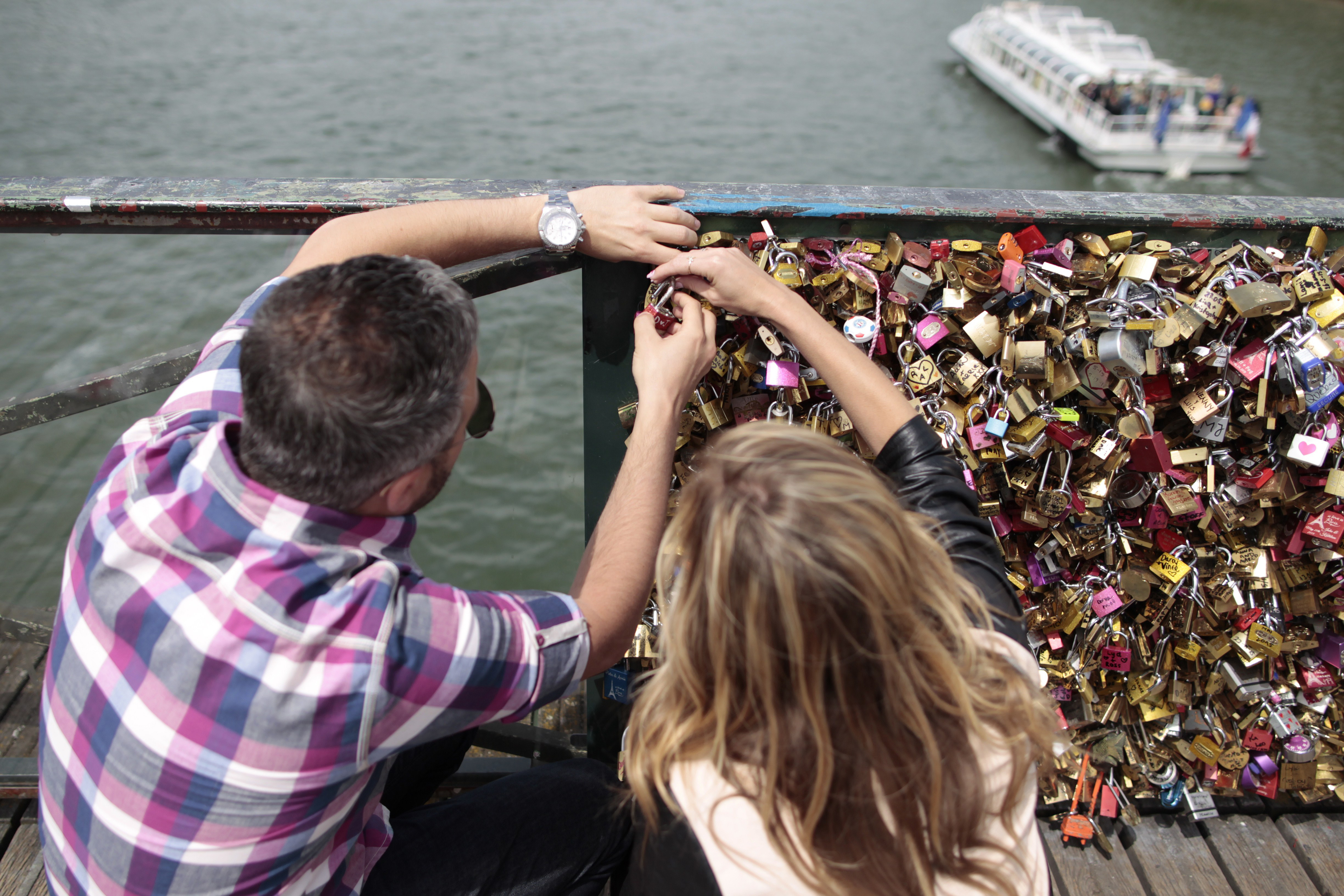 A couple locks a padlock on the Pont des Arts on May 29, 2015, in Paris as the Paris municipality announced that the bridge's fences have to be removed due to the weight of the padlocks put by tourists to symbolize everlasting love