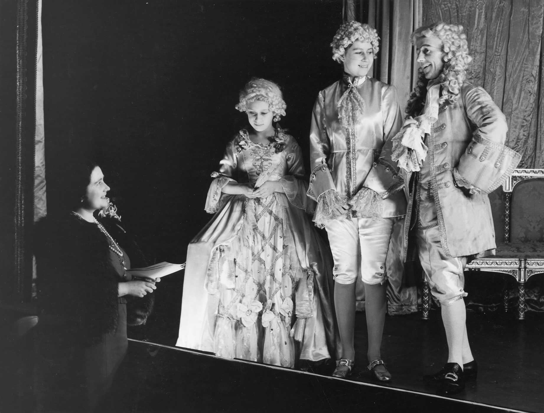 Queen Elizabeth, Princess Margaret and Princess Elizabeth stage a rehearsal of Cinderella on Dec. 21, 1941, the first royal pantomime at Windsor Castle. Both Elizabeth and Margaret were educated at home, with lessons concentrating on history, language, literature and music.