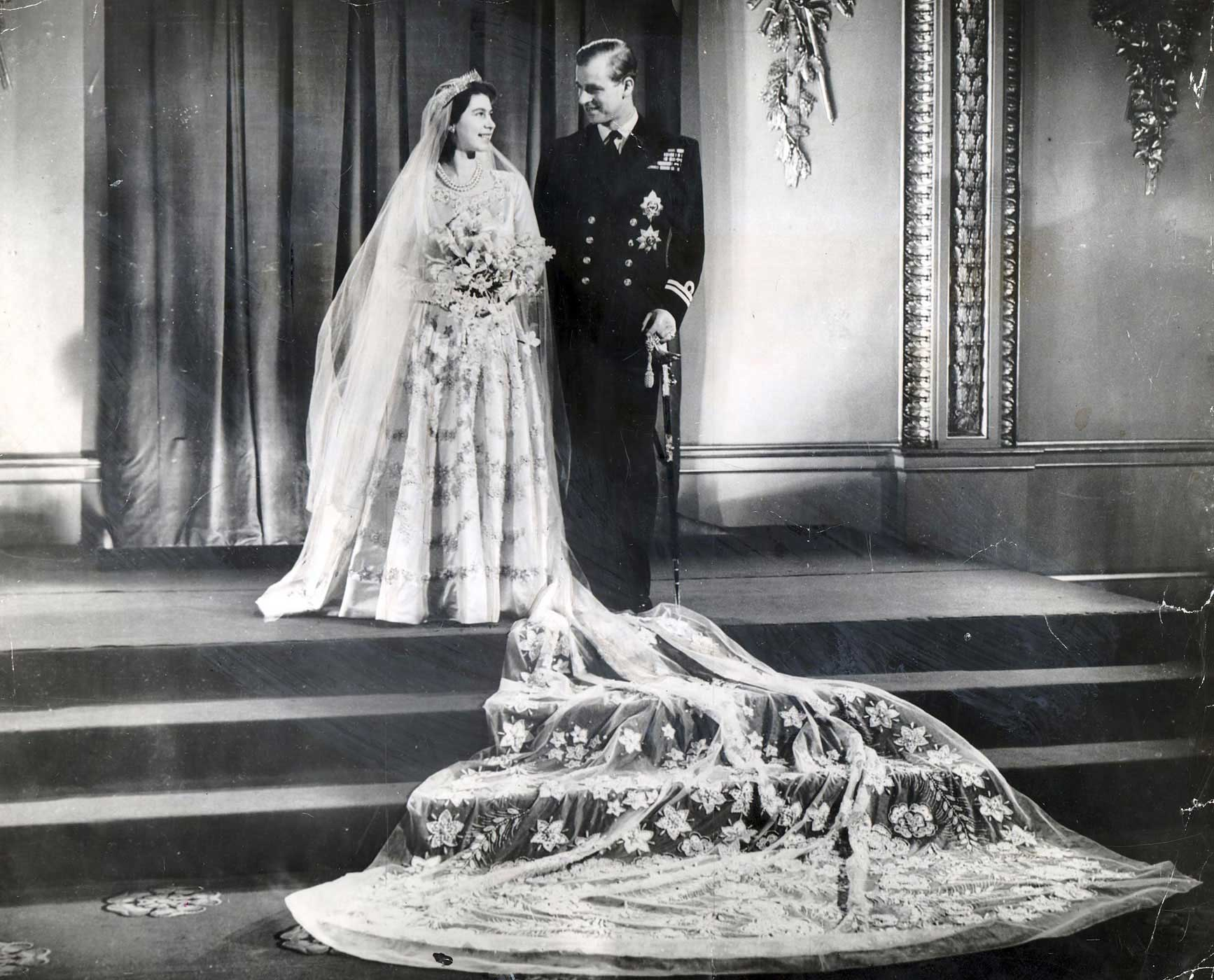 The happy royal couple, photographed on their wedding day, Nov. 20, 1947, at Buckingham Palace. Elizabeth's dress was designed by Sir Norman Bishop Hartnell and was purchased with ration coupons because of the economic hardship Britain faced after the war.
