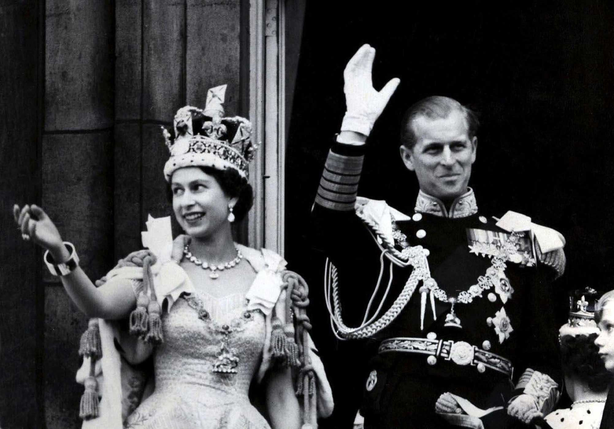 The newly named Queen Elizabeth II and the Duke of Edinburgh wave from a balcony to the crowds at the gates of Buckingham Palace after the coronation on June 2, 1953. Norman Hartnell designed Elizabeth's coronation gown; she had specifically requested that it be embroidered with the national flowers of each Commonwealth country.