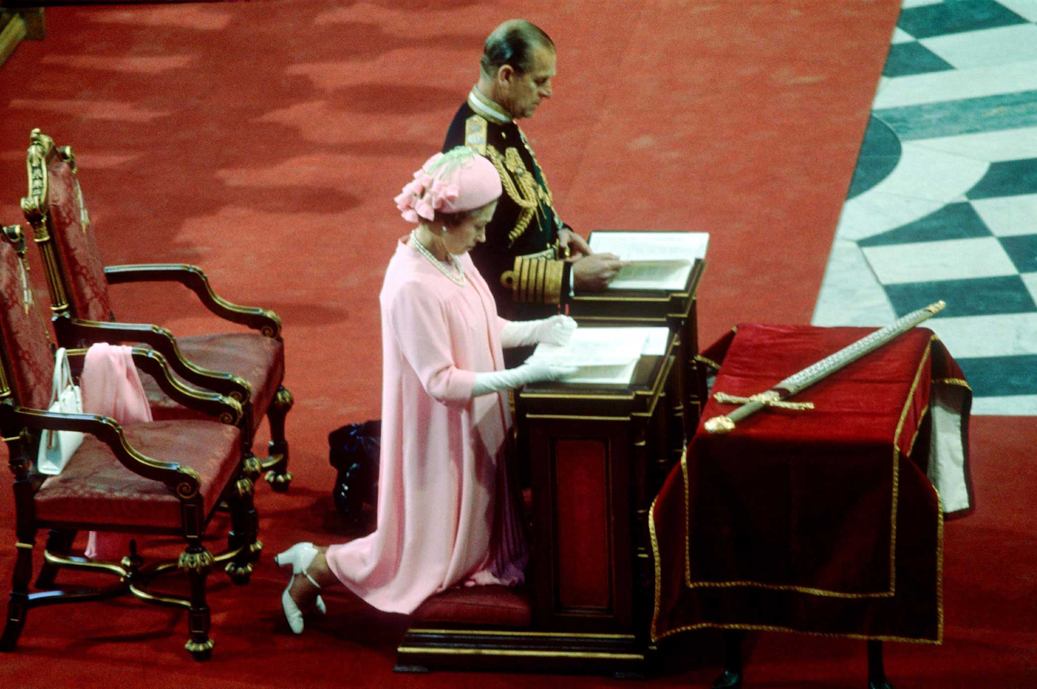 Queen Elizabeth II and Prince Philip kneel during a ceremony for the Queen's Silver Jubilee in 1977. Celebrations throughout Britain and the Commonwealth reaffirmed the monarch's popularity among the public.