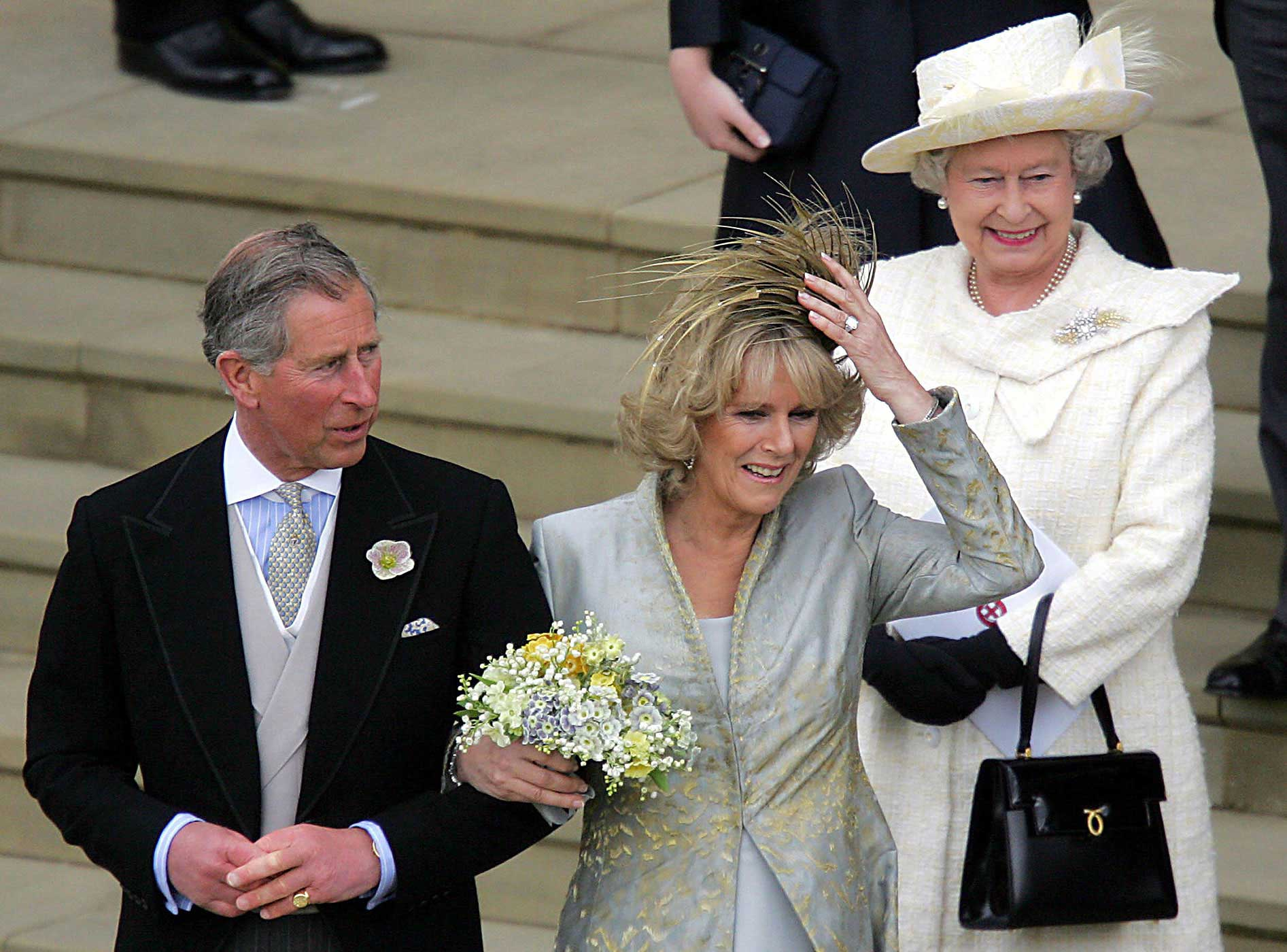 Prince Charles and Camilla, Duchess of Cornwall, smile as they leave St. George's Chapel on their wedding day on April 9, 2005. Queen Elizabeth II, who gave the longtime lovers her blessing, looks on.