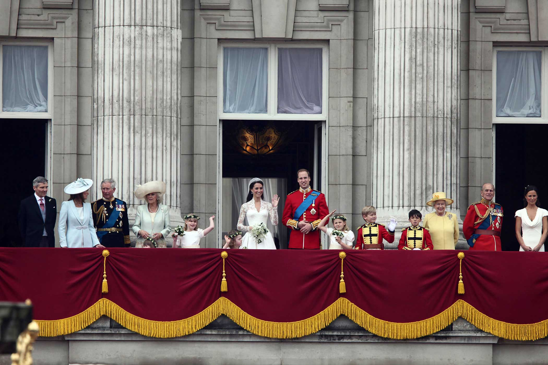 "Prince William stands with his bride, Catherine, Duchess of Cambridge, on a balcony at Buckingham Palace, surrounded by family, on April 29, 2011. The future King's marriage to his longtime girlfriend, a commoner by birth and the first female member of the royal family to graduate from a university, marked a shift in the mores of the monarchy. The Queen officially approved the marriage, as required under the Royal Marriages Act of 1772, by signing a document stating that she accepts the union between her grandson and the ""well-beloved"" Kate Middleton."
