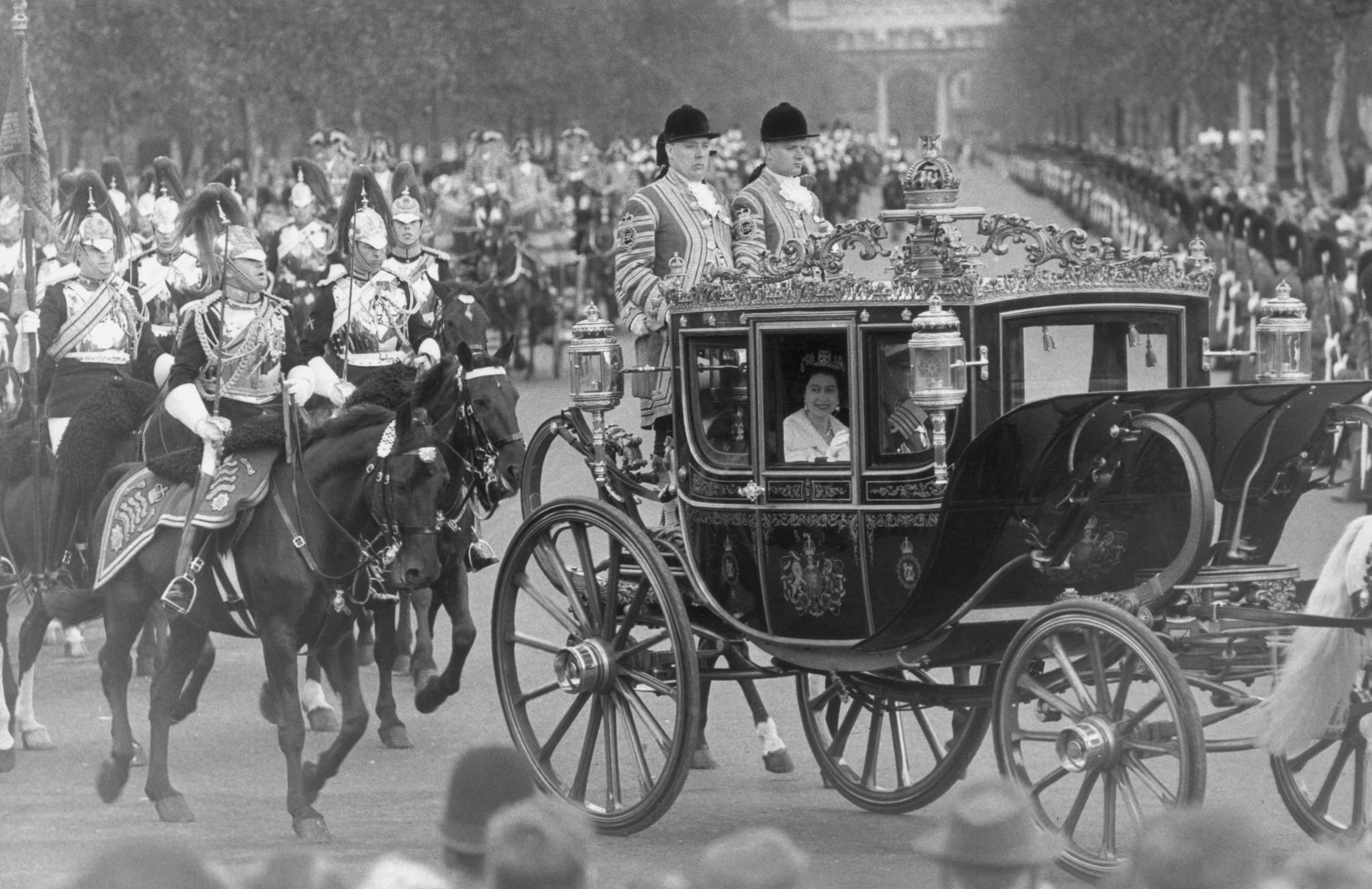 Queen Elizabeth II drives past the Victoria Memorial outside Buckingham Palace in the Irish State Coach, on her way to take part in the State Opening Of Parliament in 1962.