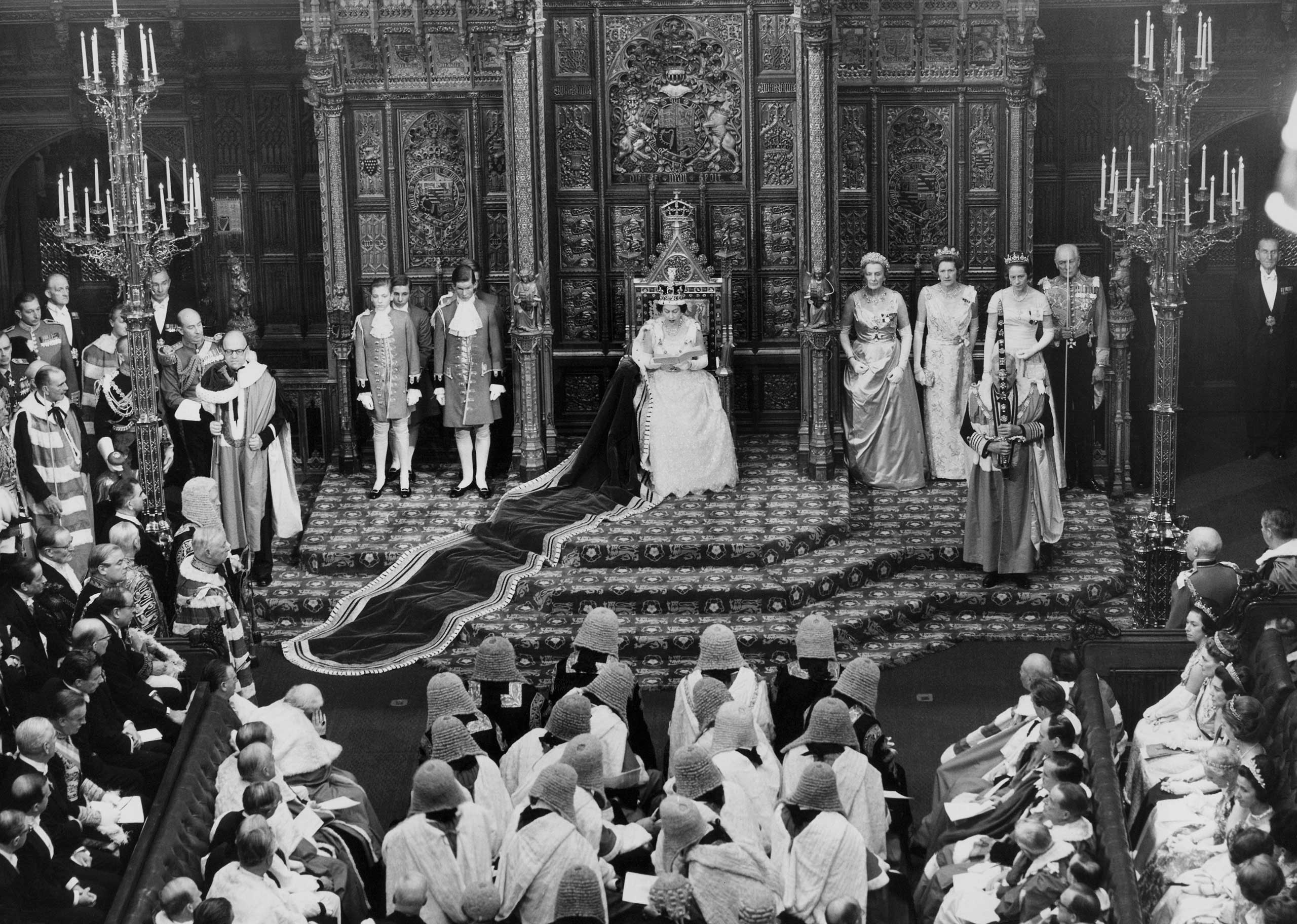 Queen Elizabeth II reads her speech from the throne in the House of Lords as she formally opens the new parliament in London in 1964.