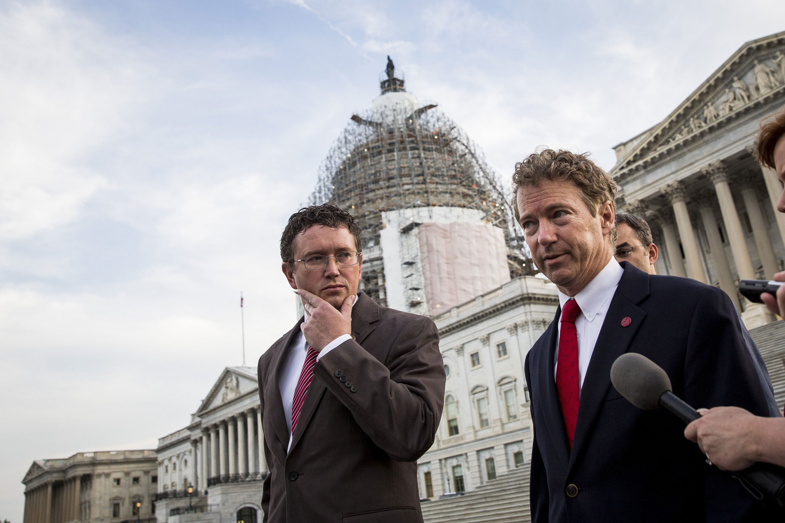 From left: Representative Thomas Massie listens as Senator Rand Paul speaks to reporters after exiting the Senate chamber on Capitol Hill in Washington on May 31, 2015.