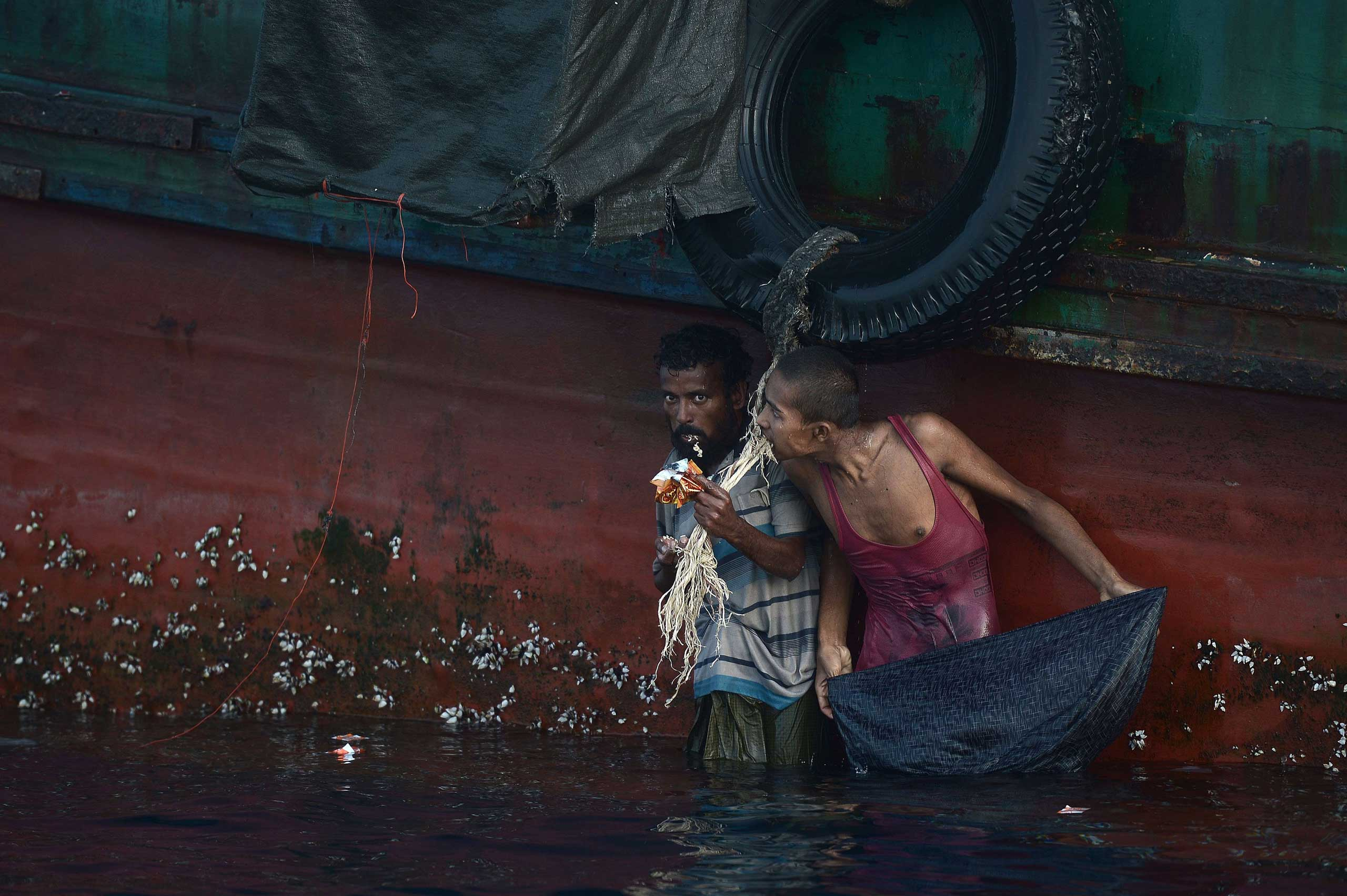 A Rohingya migrant eats food dropped by a Thai army helicopter after he jumped to collect the supplies at sea from a boat drifting in Thai waters off the southern island of Koh Lipe in the Andaman sea on May 14, 2015.