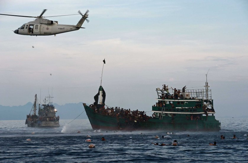 Rohingya migrants swim to collect food supplies dropped by a Thai army helicopter after they jumped from a boat drifting in Thai waters off the southern island of Koh Lipe in the Andaman sea on May 14, 2015.