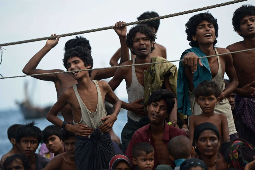 Rohingya migrants stand and sit on a boat drifting in Thai waters off the southern island of Koh Lipe in the Andaman sea between Thailand and Malaysia on May 14, 2015.