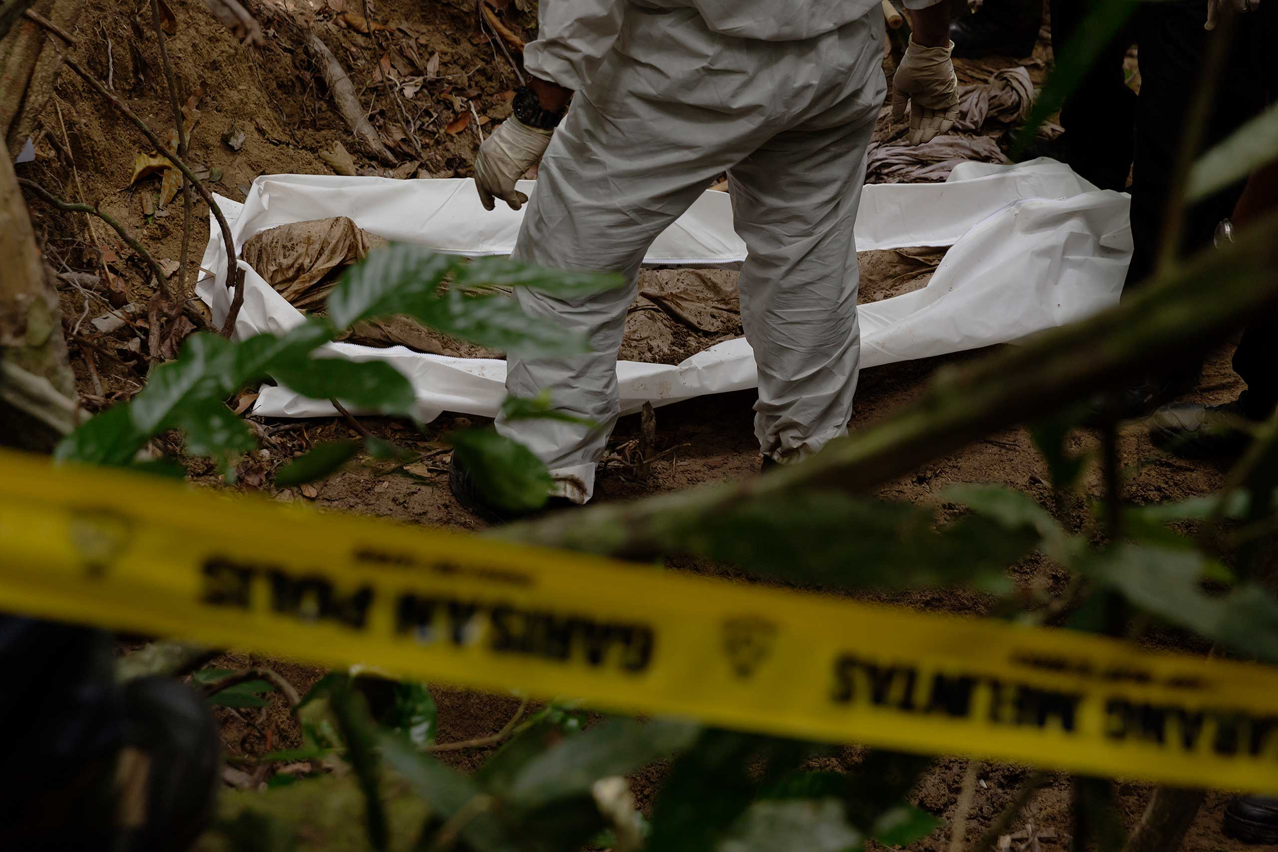 Human remains being disinterred from an informal cemetery near an abandoned camp allegedly for trafficked Rohingya and Bangladeshis in mountainous jungle on the Malaysian side of the Thai-Malaysian border.