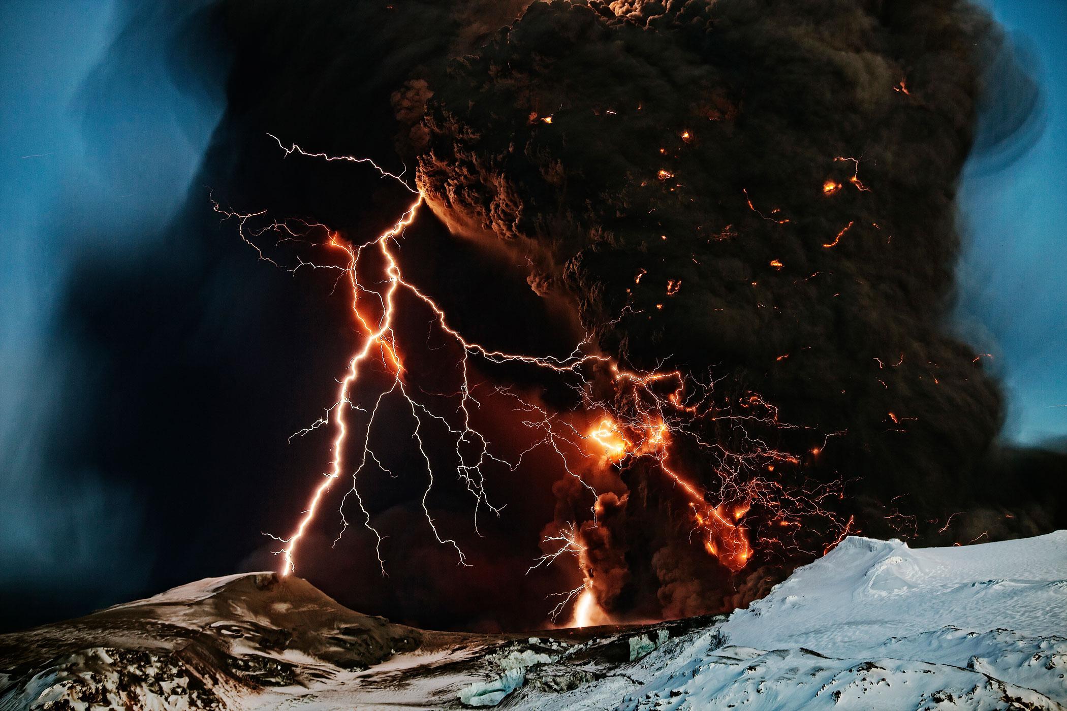 Lightning streaks across the sky as lava flows from a volcano in Eyjafjallajokul, April 17, 2010.