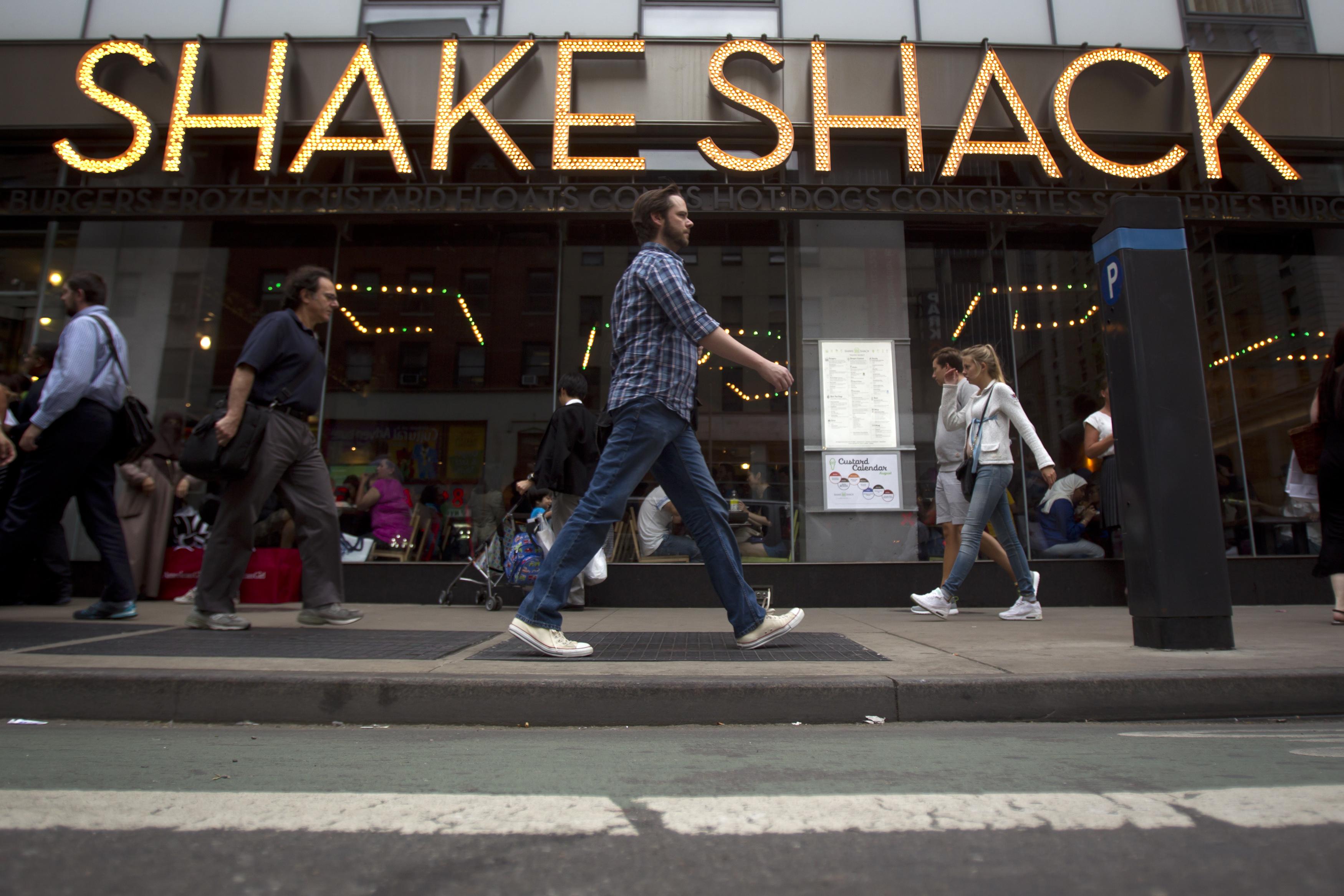 People walk past a Shake Shack restaurant in the Manhattan borough of New York August 15, 2014.