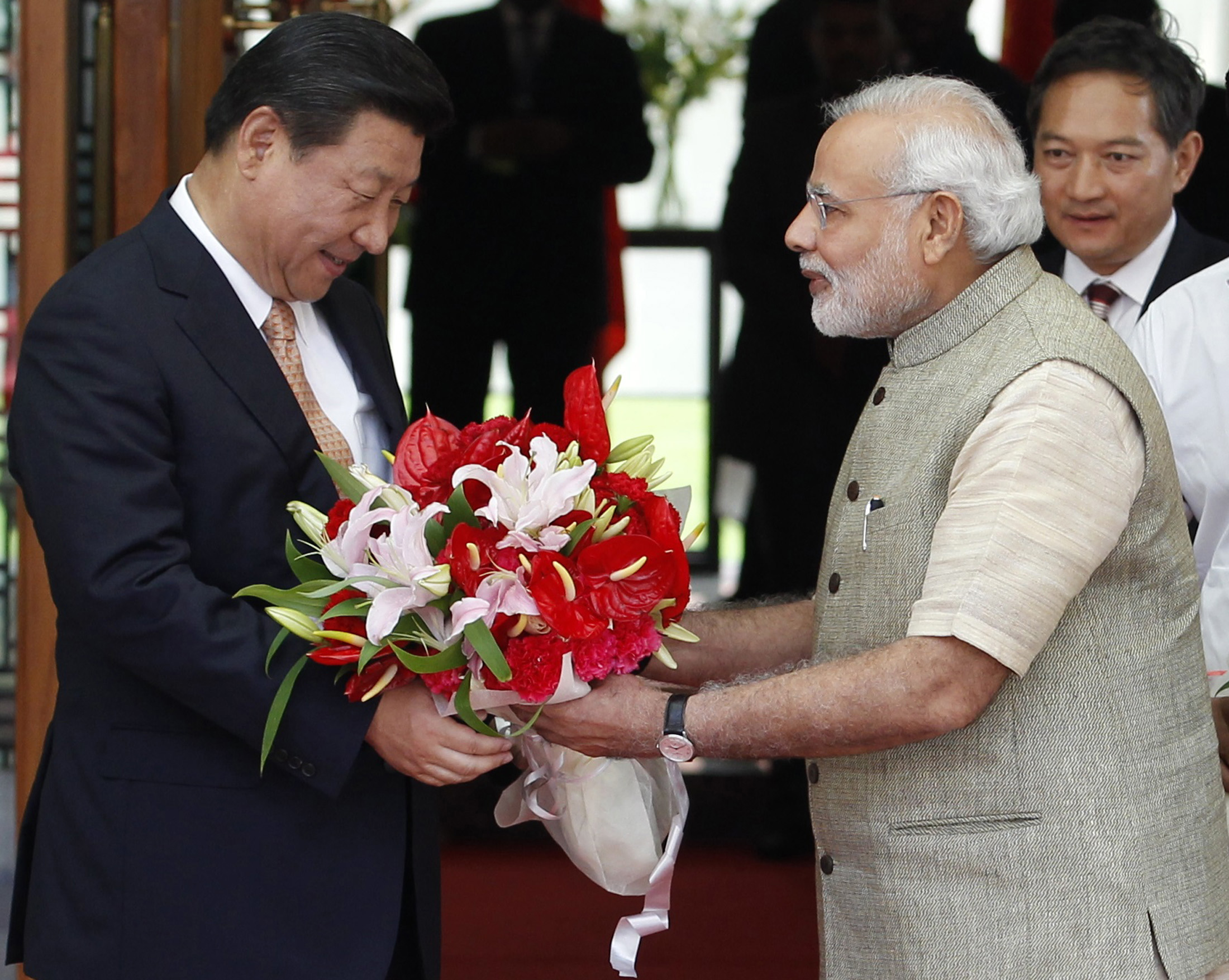 India's Prime Minister Narendra Modi, right, presents a bouquet to China's President Xi Jinping before their meeting in the western Indian city of Ahmedabad on Sept. 17, 2014