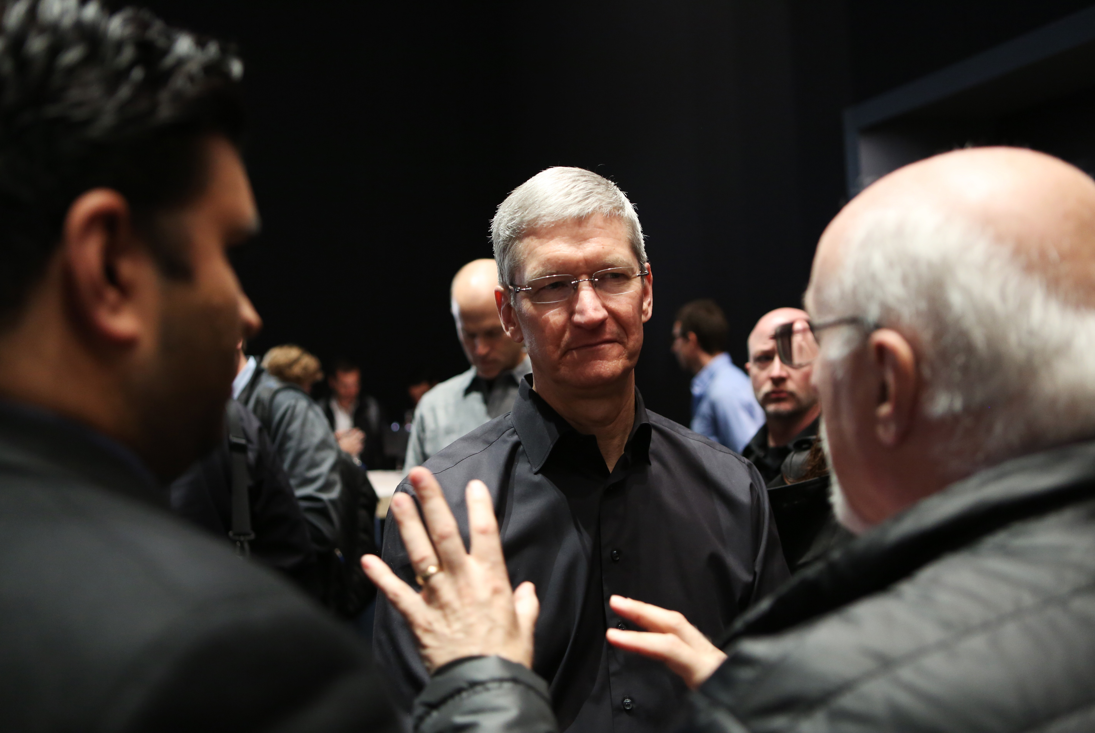 Walt Mossberg, Recode's co-founder (right foreground), speaks with Apple CEO Tim Cook.
