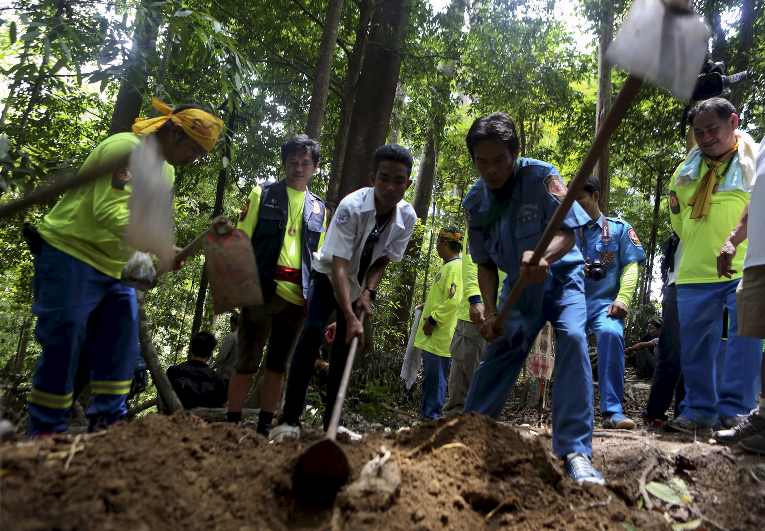 Rescue workers inspect a mass grave at an abandoned camp in a jungle in Thailand's southern Songkhla province on May 5, 2015