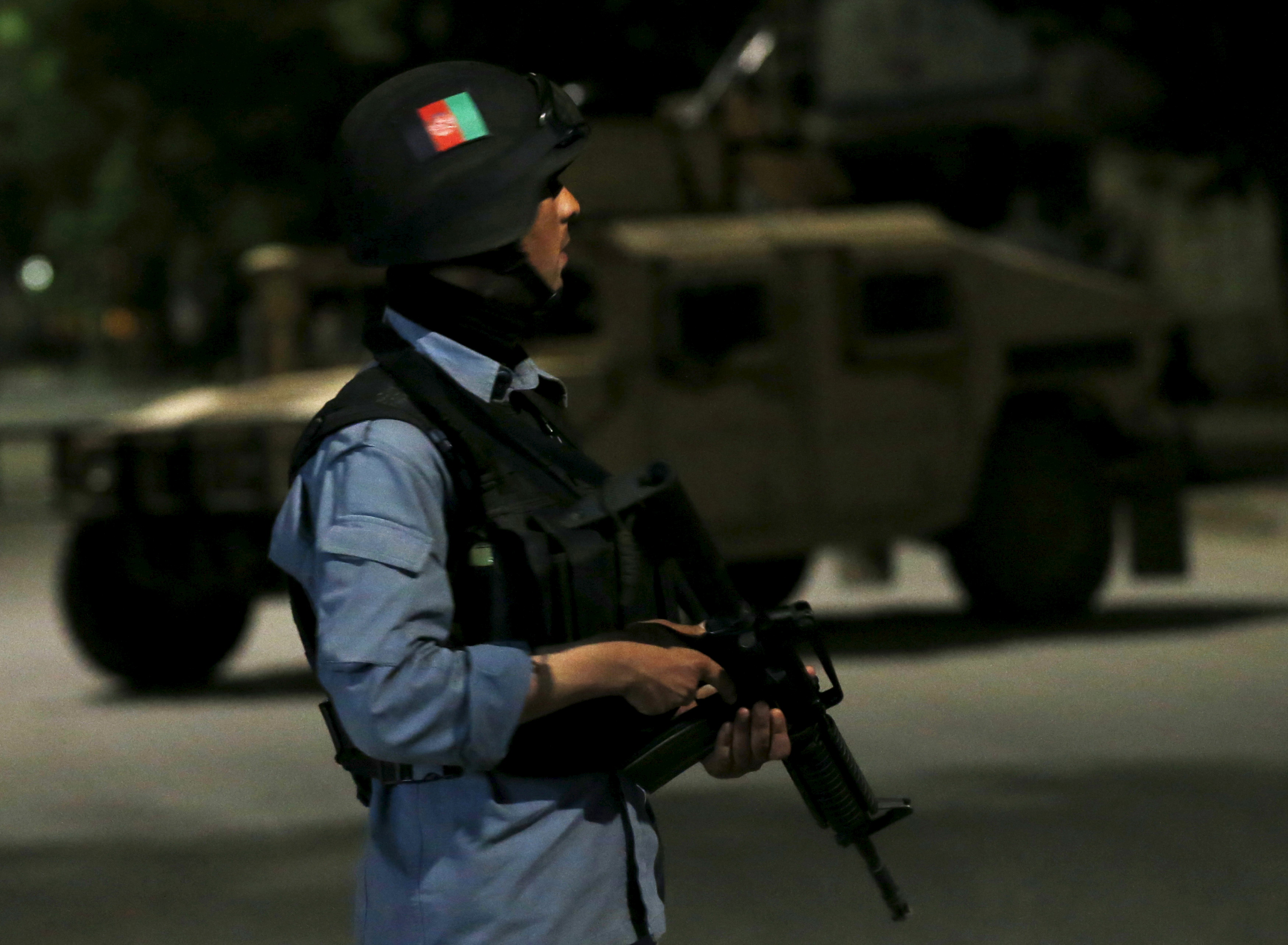 An Afghan policeman stands guard at the site of an attack in Kabul, Afghanistan May 13, 2015.
