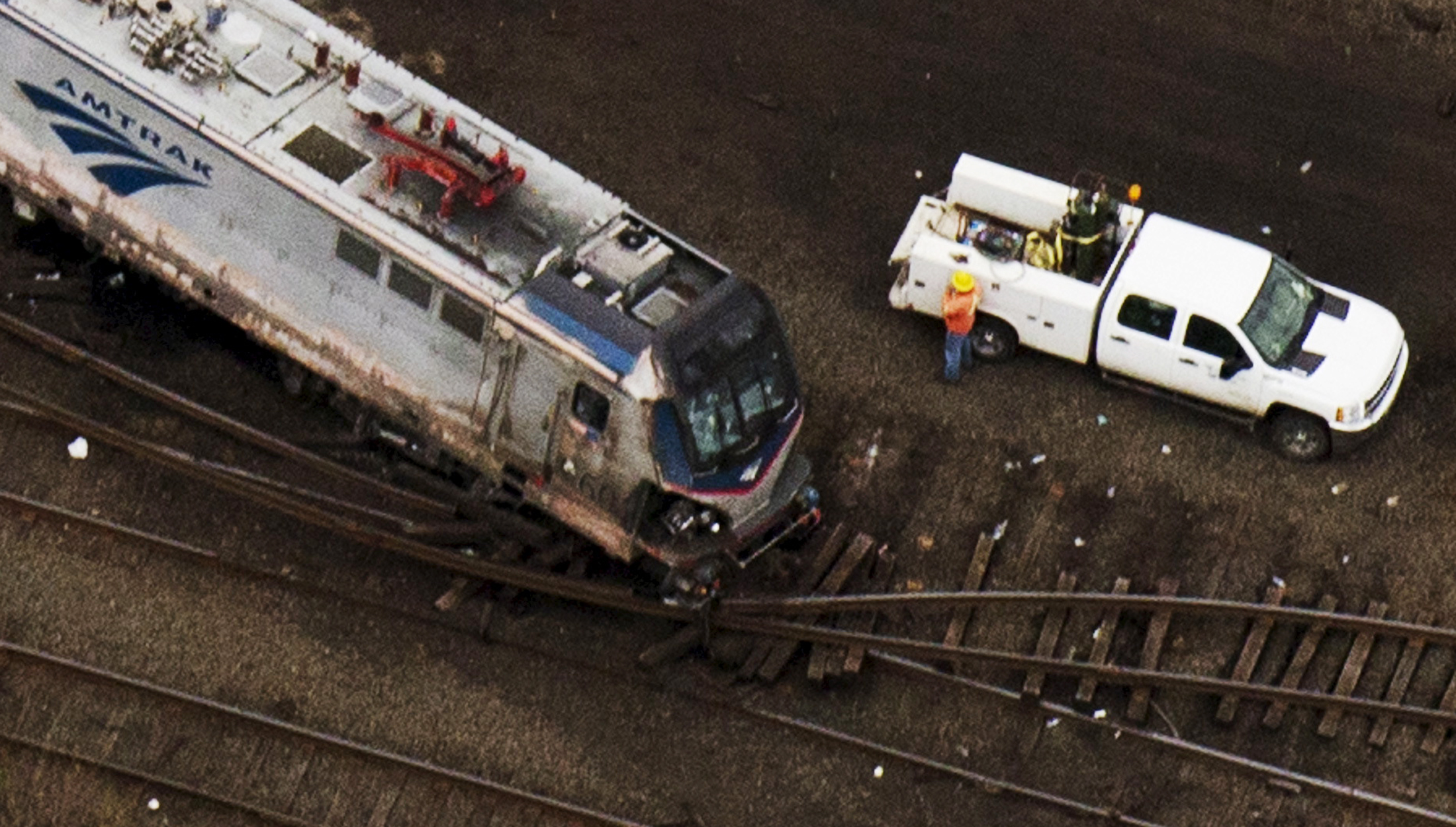 Emergency workers look through the remains of a derailed Amtrak train in Philadelphia, Pennsylvania in this May 13, 2015 file photo