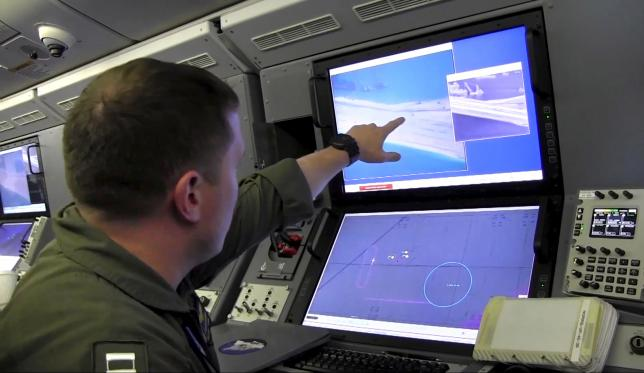 A sailor aboard a P-8 Poseidon surveillance plane points out claimed Chinese construction on Fiery Island Reef during a flight last week.