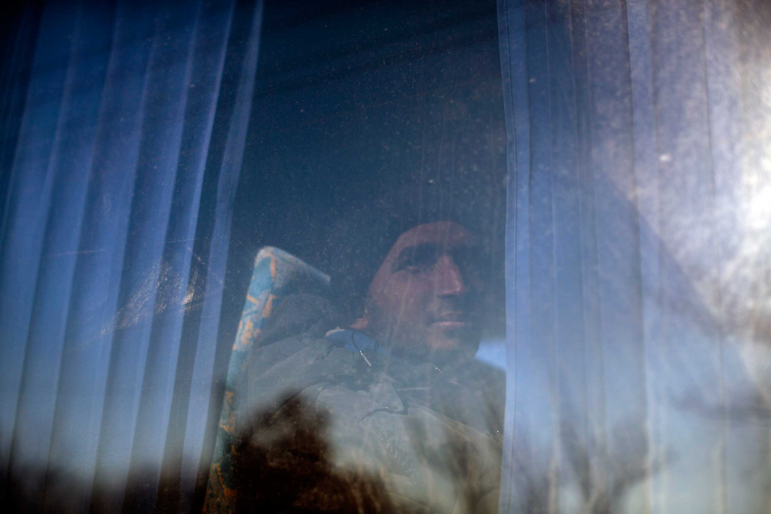 A migrant detained by the Hungarian police after illegally crossing the border with Serbia peers out of a window of a police bus in Asotthalom, some 110 miles southeast of Budapest, Hungary, on Feb. 18, 2015.