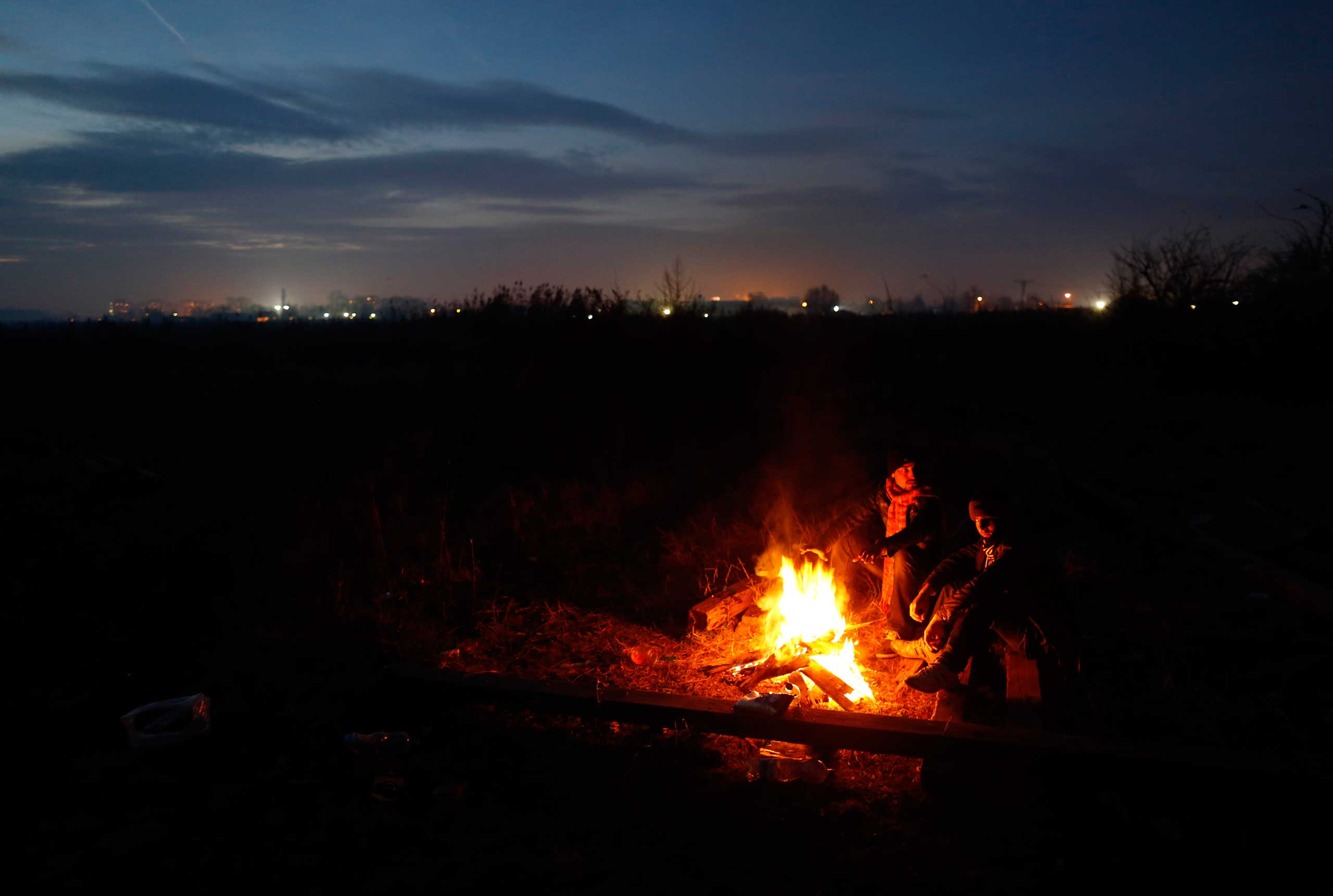Migrants gather around the fire which they use for cooking and for warmth in the abandoned brick factory in the northern Serbian town of Subotica, near the border between Serbia and Hungary, on Dec. 15, 2014.