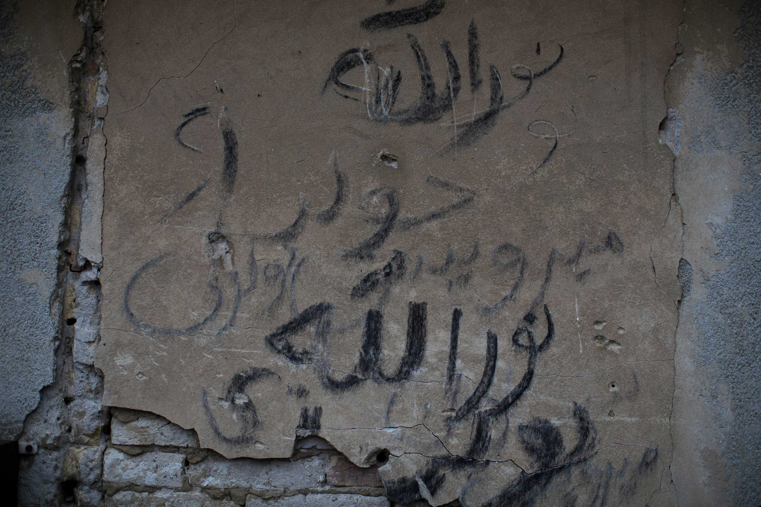 A graffiti in Arabic letters is seen on a wall of an abandoned factory used as a resting point by migrants on the outskirts of Subotica, 90 miles north of Belgrade, Serbia on Feb. 26, 2015.