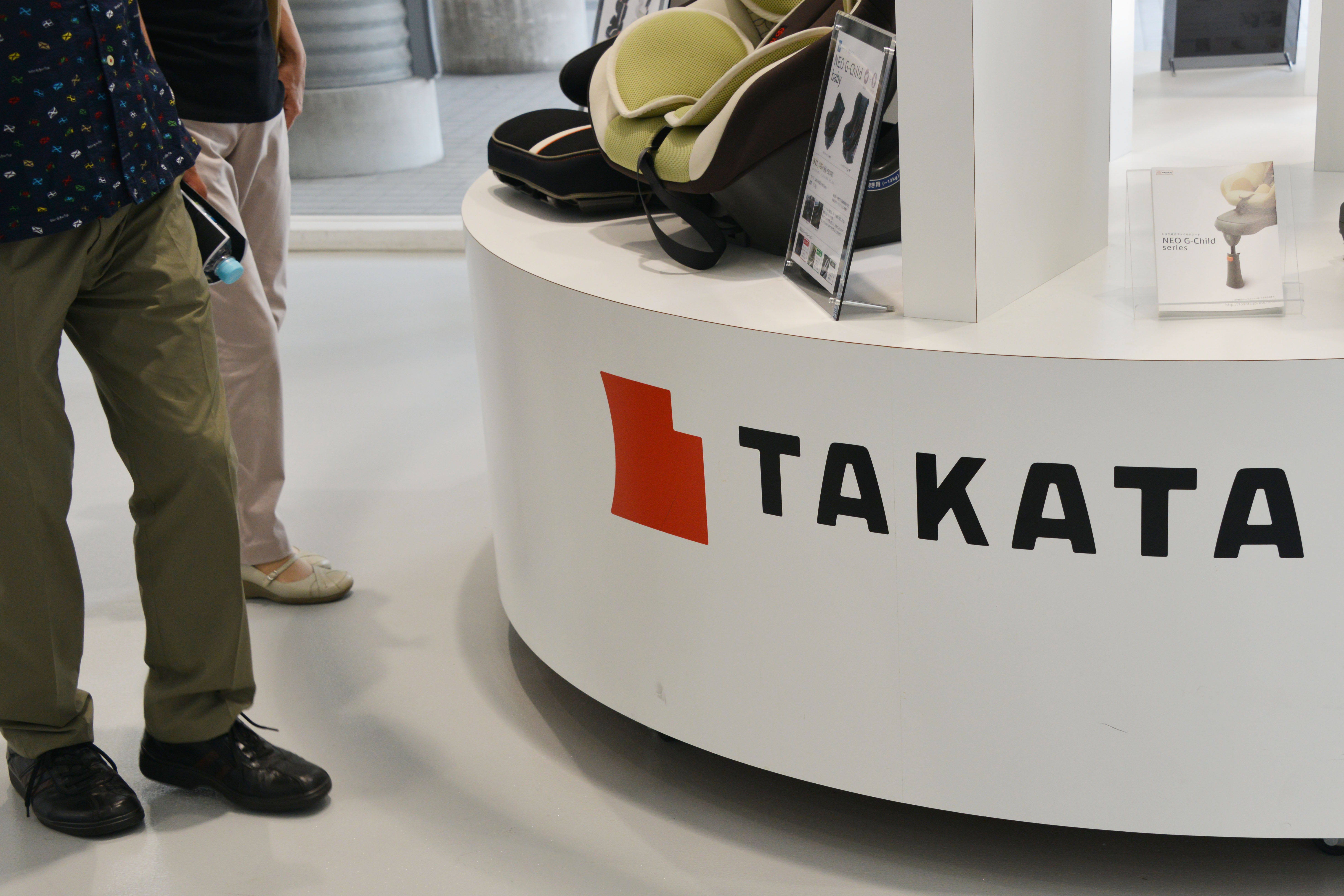 A visitor walks past displays of Takata Corp at a showroom for vehicles in Tokyo, Japan on May 20, 2015.