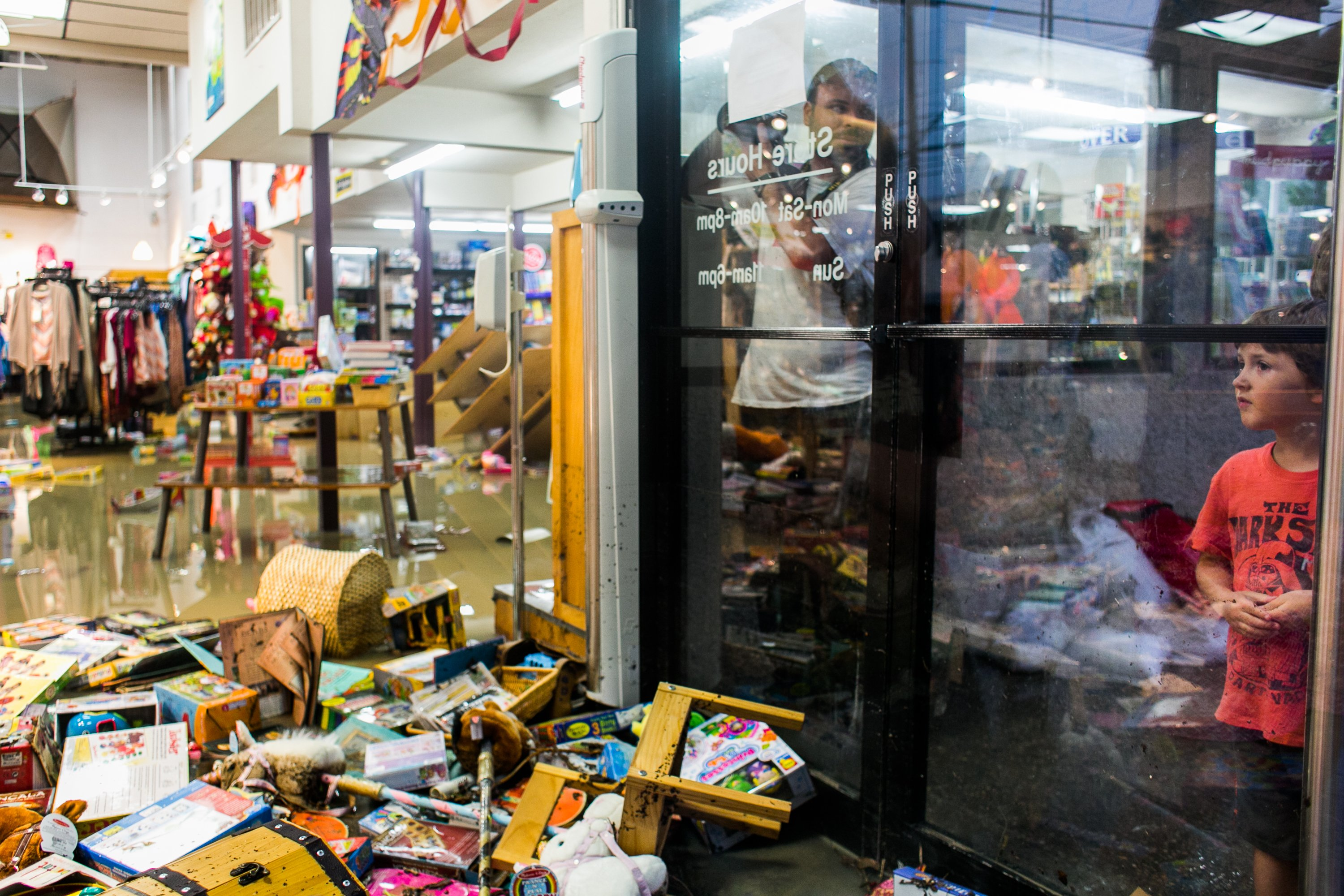 Lucas Rivas looks into the flooded Whole Earth Provisions Company after days of heavy rain in Austin on May 25, 2015.