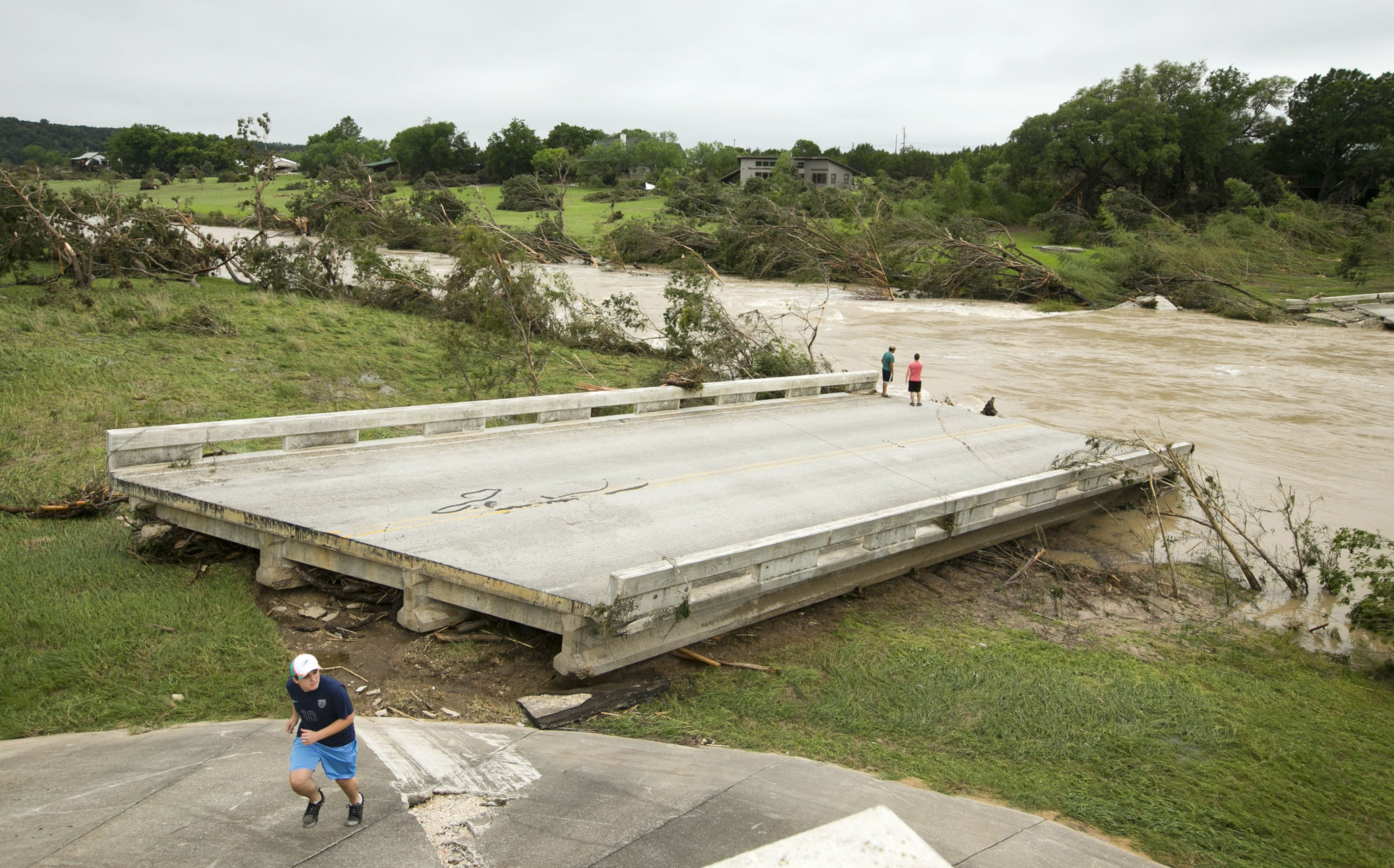 Dustin McClintock, Brandon Bankston, and Hesston Krause look at the destroyed remains of the Fischer Store Road bridge over the Blanco River near Wimberley, Texas on May 24, 2015.