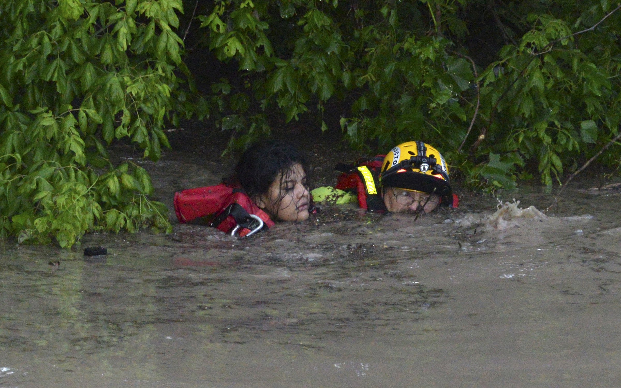San Marcos Firefighter Jay Horton rescues a woman from the flood waters in San Marcos, Texas on May 24, 2015.