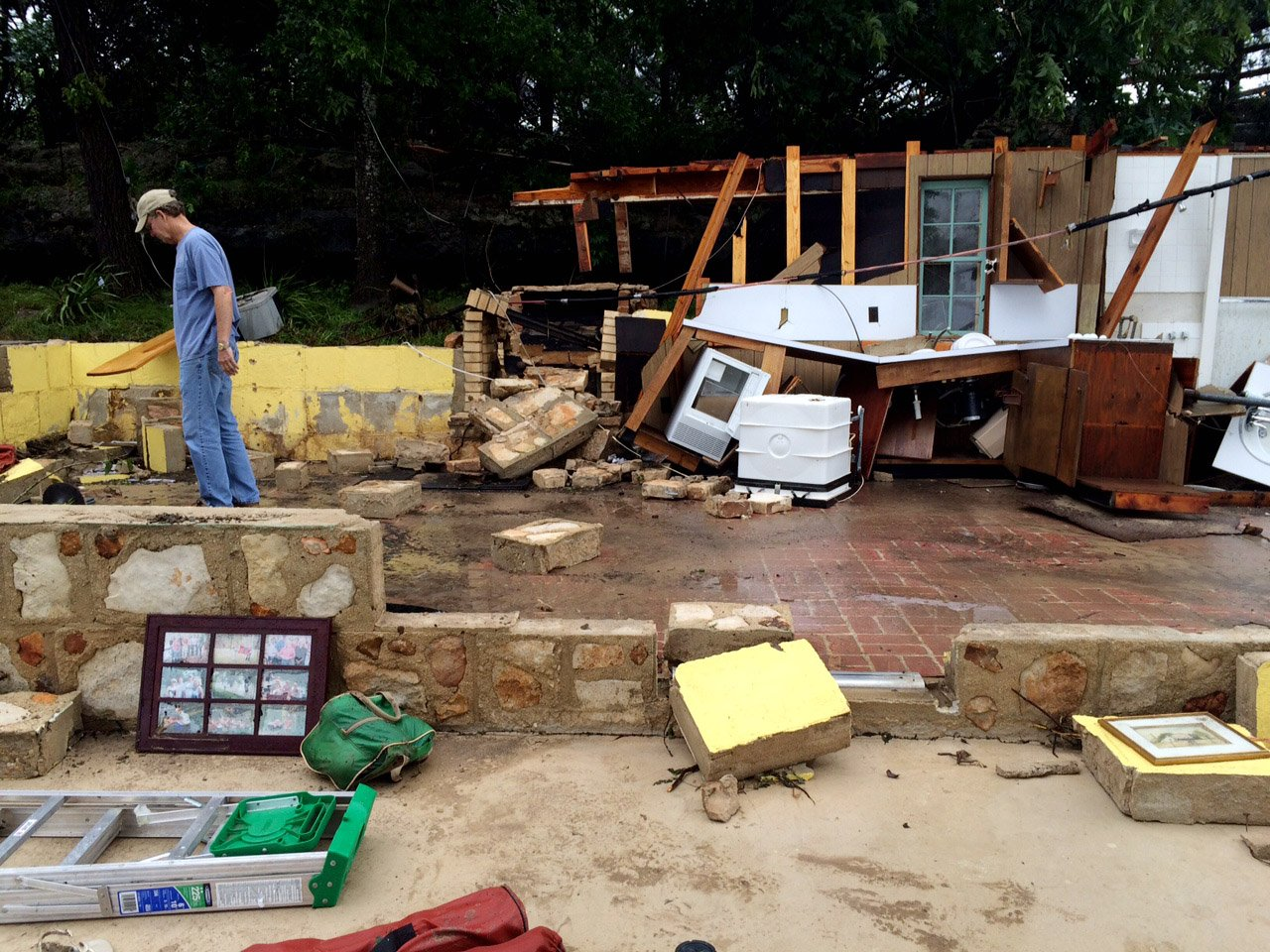 Gordon Welch surveys damage to the house his family has owned since 1964 along River Road next to the Blanco River in Wimberley, Texas, May 24, 2015.