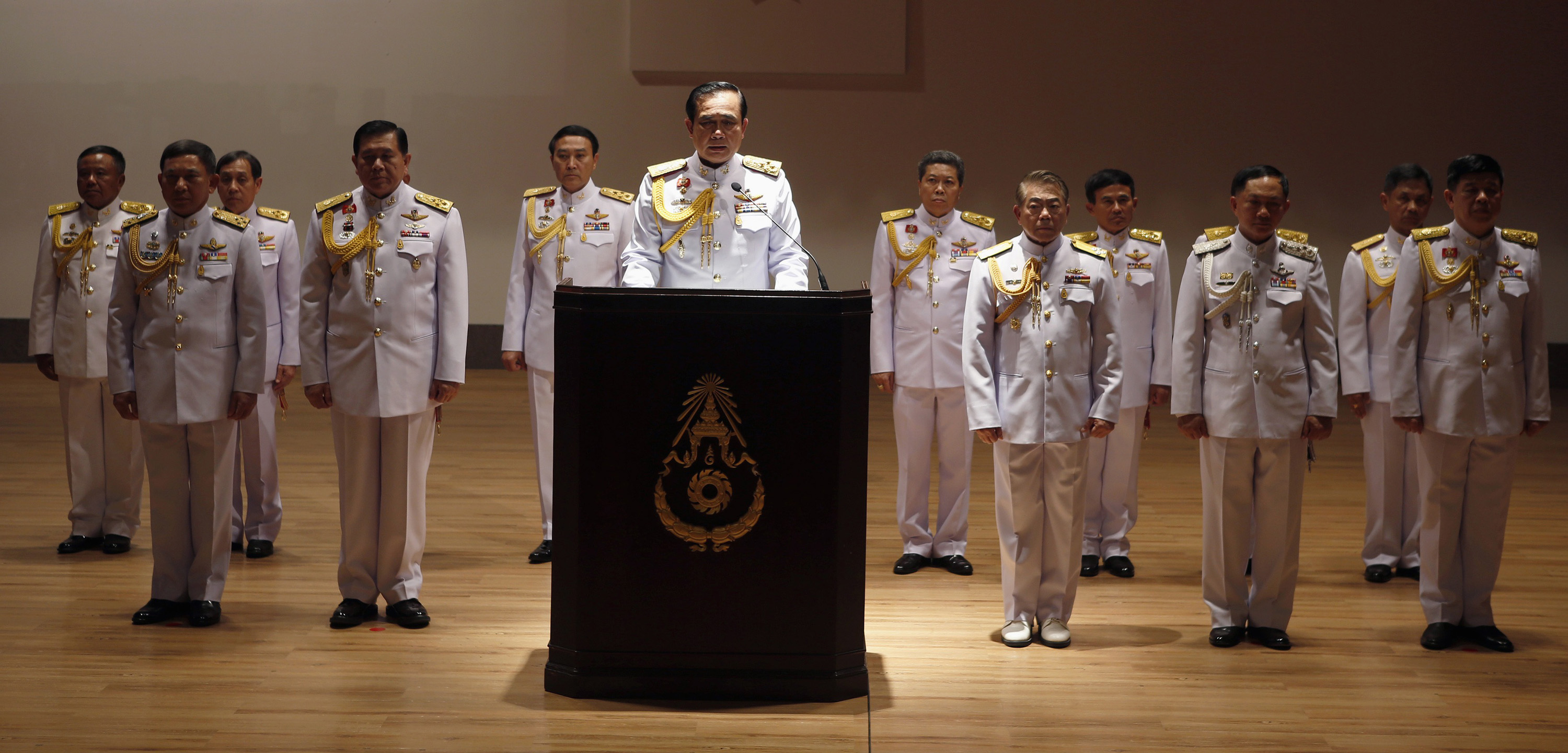 Prayuth, with his top officers, addresses reporters in Bangkok on May 26 last year after taking power as the head of the junta.