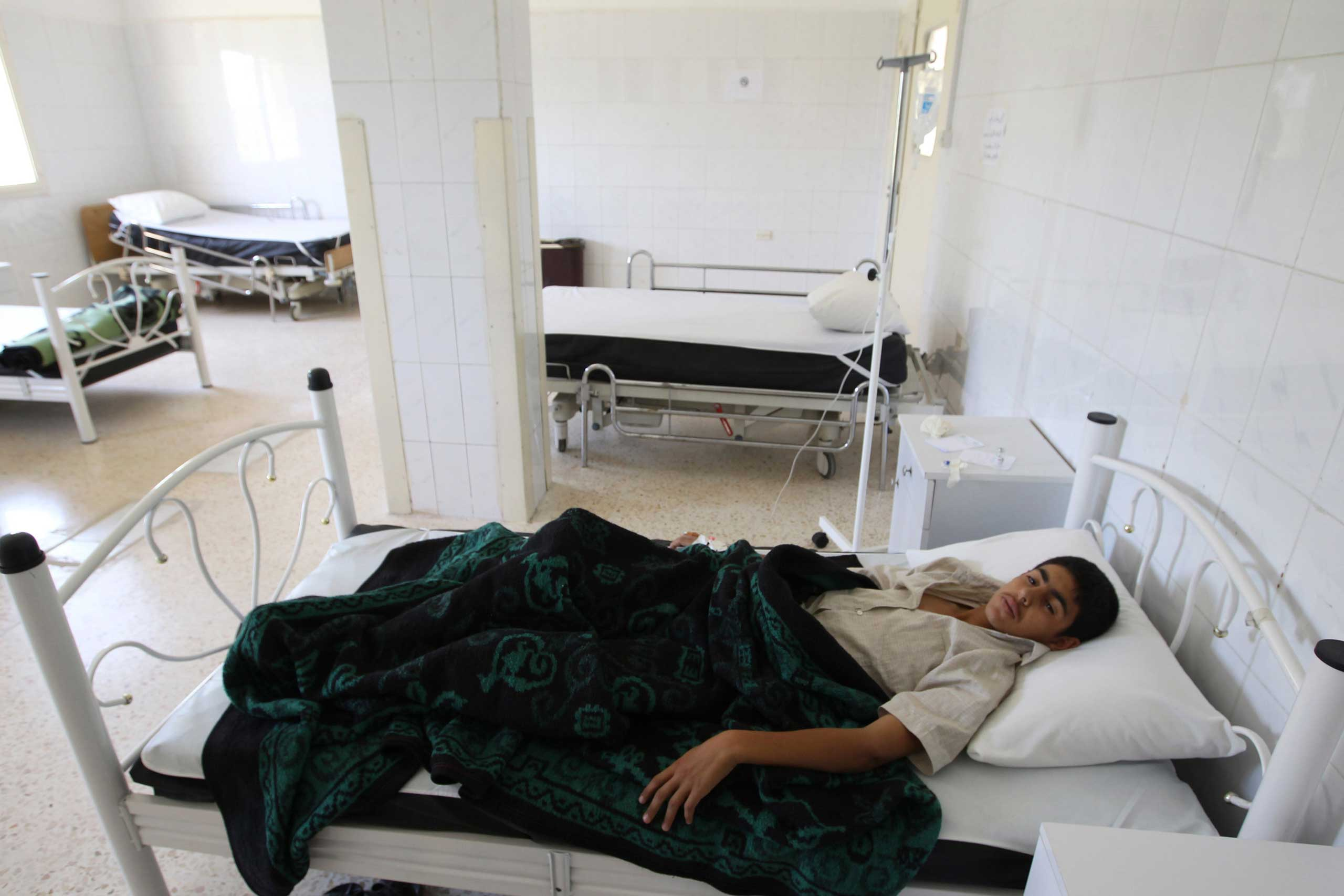 A boy infected by typhoid from polluted water, lies at a hospital in al-Qouniya village in Idlib, Syria, May 27, 2013.
