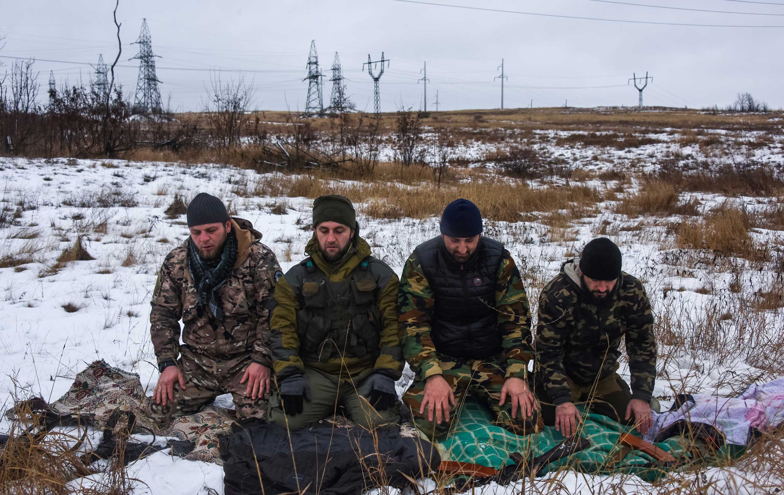 Muslim Chechen men, who fight alongside pro-Russian rebels, pray near a checkpoint in the town of Zugres, Eastern Ukraine, on Jan. 11, 2015.