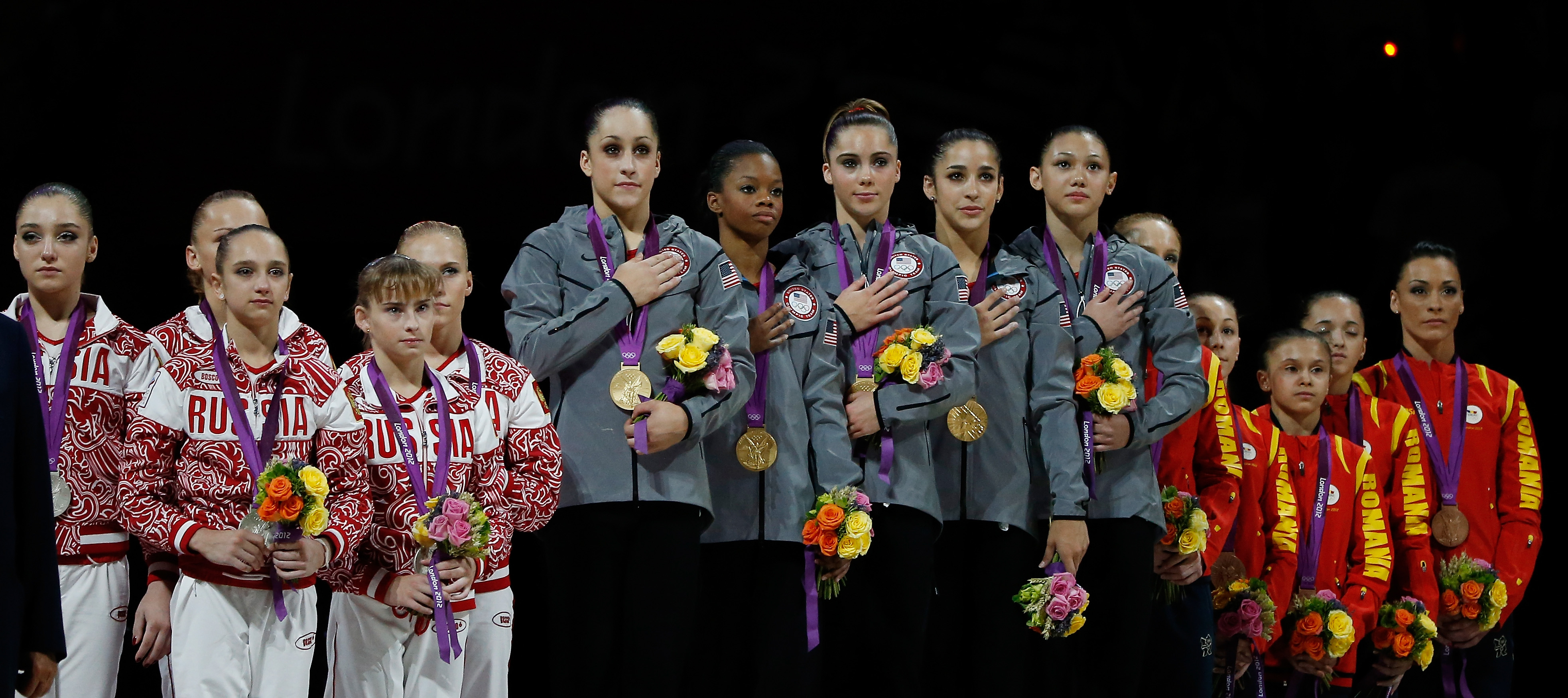 Silver medalists Russia, gold medalists United States with Aly Raisman second from right, and bronze medalists Romania pose of the podium after the Artistic Gymnastics Women's Team final on Day 4 of the London 2012 Olympic Games at North Greenwich Arena on July 31, 2012 in London.